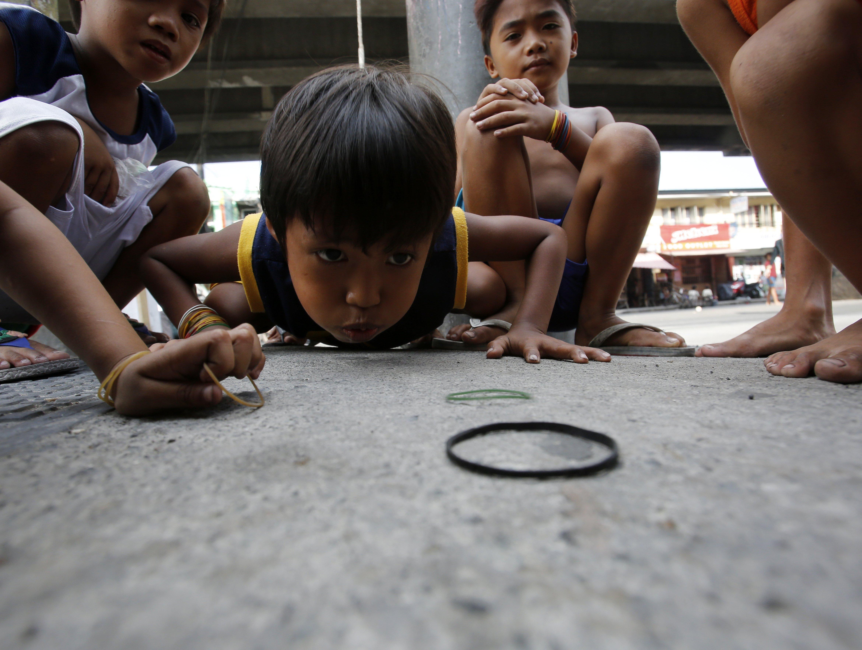 Nins filipins juguen en un barri prop de la Cimera de Països del Sud-est Asiàtics (ASEAN) a Manila (Filipines). /FRANCIS R. MALASIG