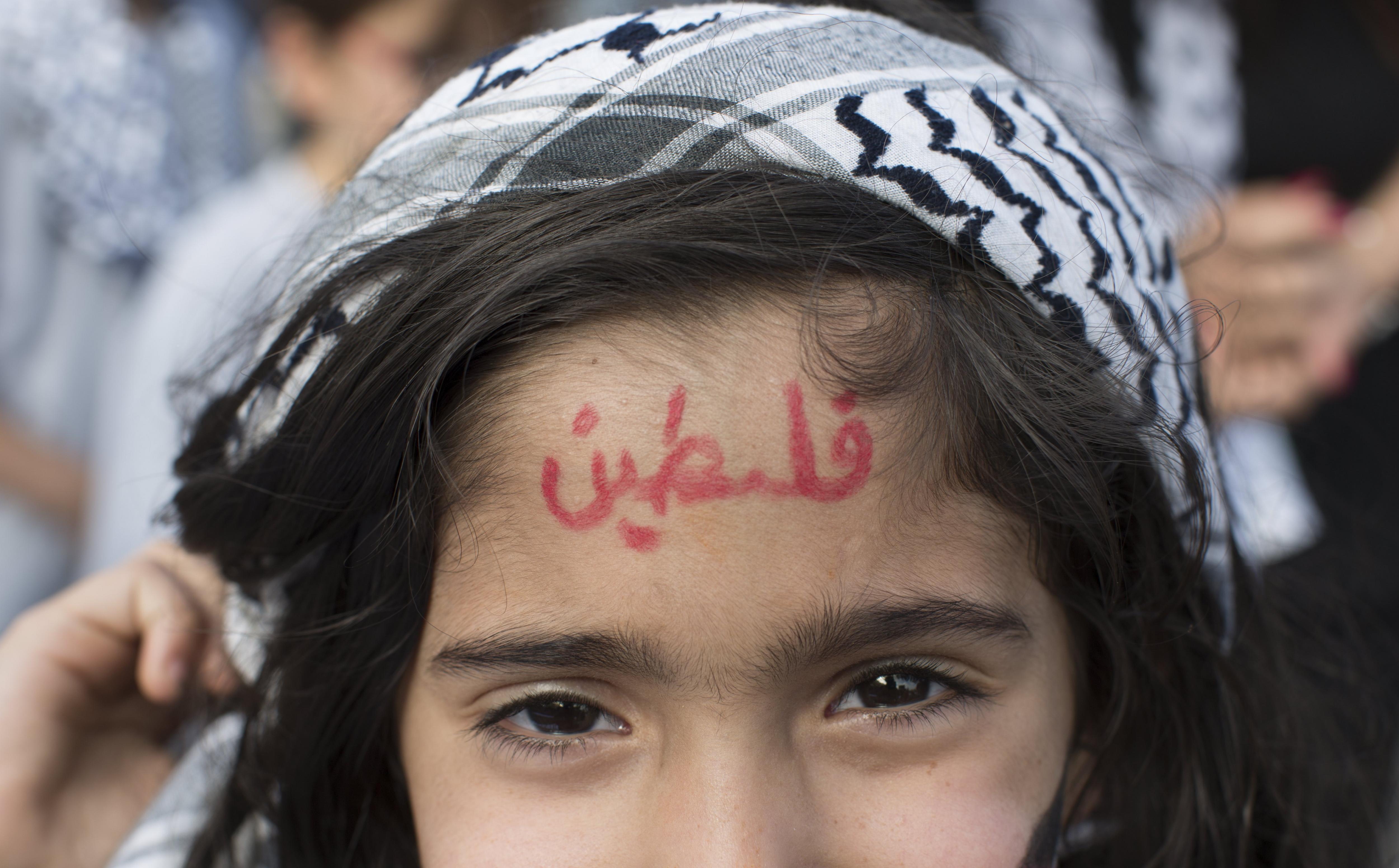 Una nina du escrita la paraula 'Palestina' en el front durant una manifestació en solidaritat dels presos palestins a les presons israelianes, a Ramallah, Palestina. /ATEF SAFADI