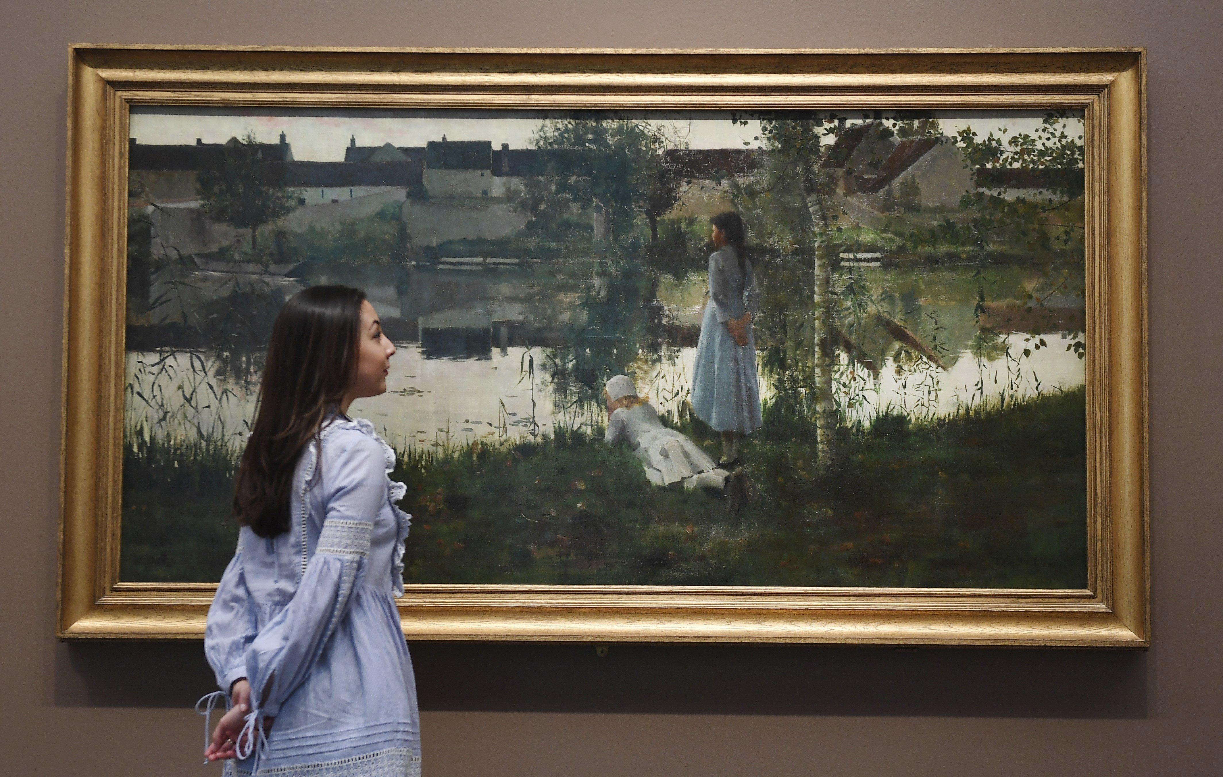 """Una empleada observa l'obra """"Le Passeur"""" de Christopher Stott (1881) en el museu Tate Britain de Londres (Reino Unido). /ANDY RAIN"""