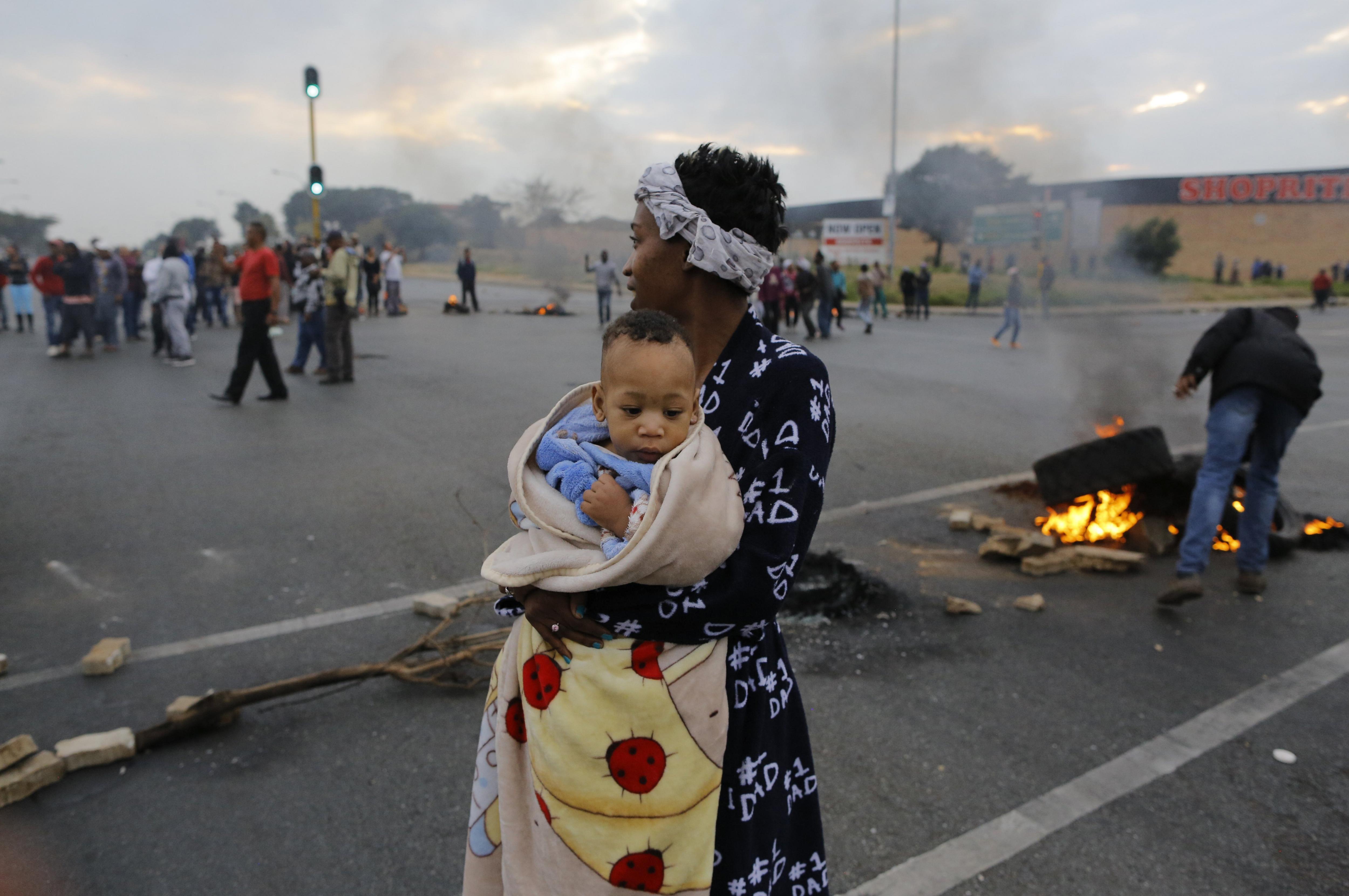 Una dona sud-africana amb el seu fill en braços se suma a la protesta per reclamar el dret a un habitatge i a un lloc de feina a Johannesburg (Sud-àfrica). /KIM LUDBROOK