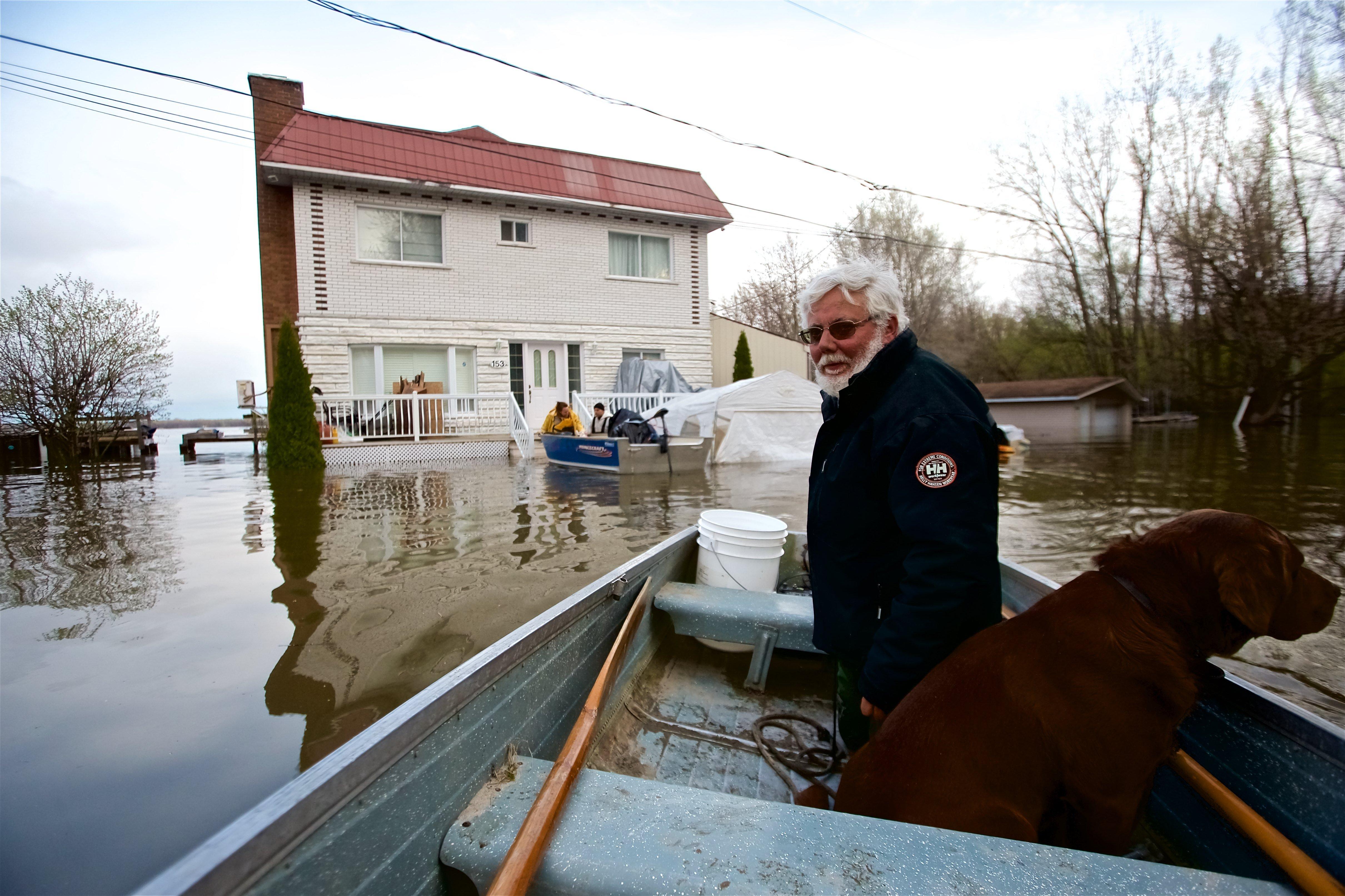 Michel Guerard i el seu ca Xoco tornen amb el seu vaixell per ajudar a evacuar les cases afectades per les inundacions, que han afectat més de 1.500 persones a Quebec (Canadà).  /VALERIE BLUM