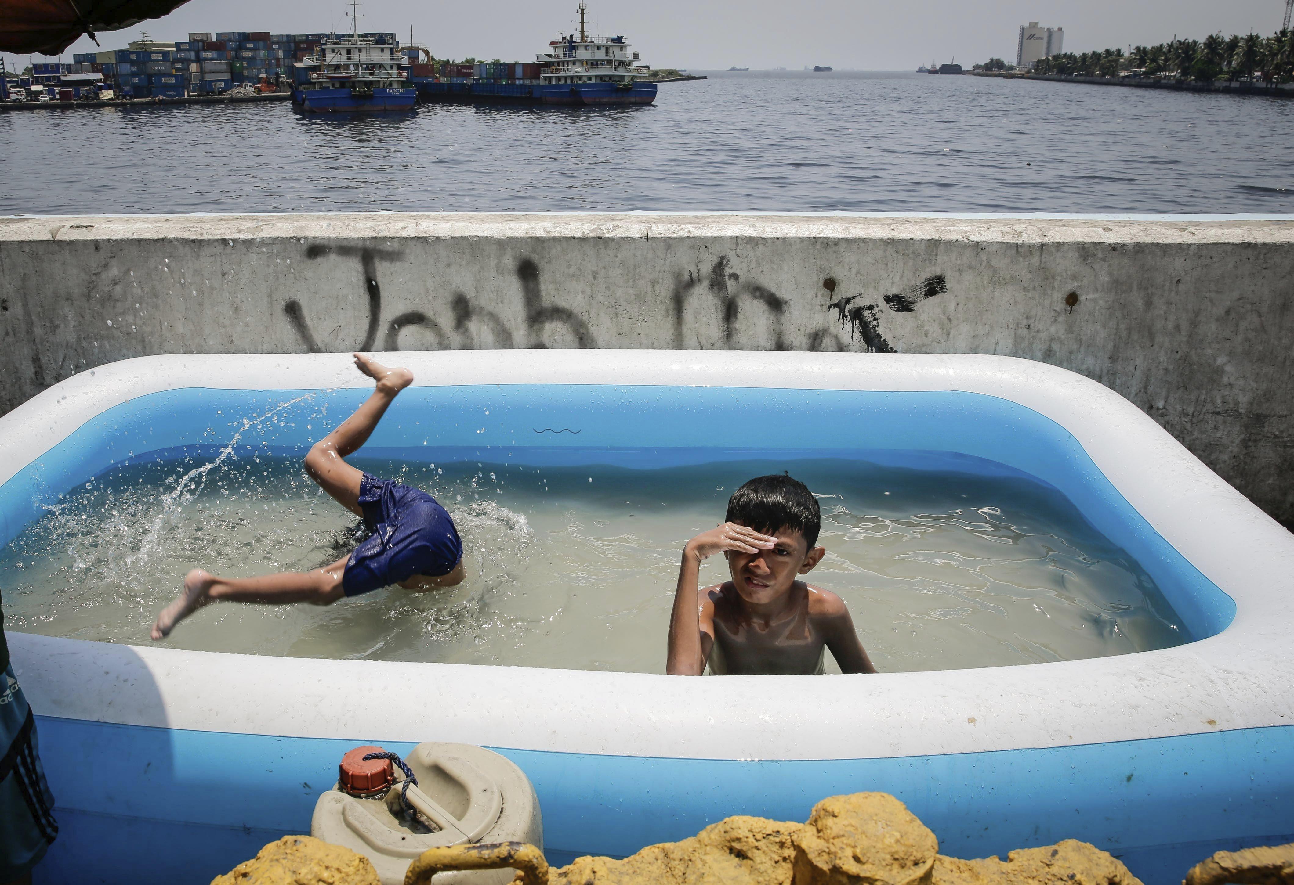 Dos nins juguen en una piscina inflable col·locada en un pont a Manila (Filipines). /MARK R. CRISTIANO