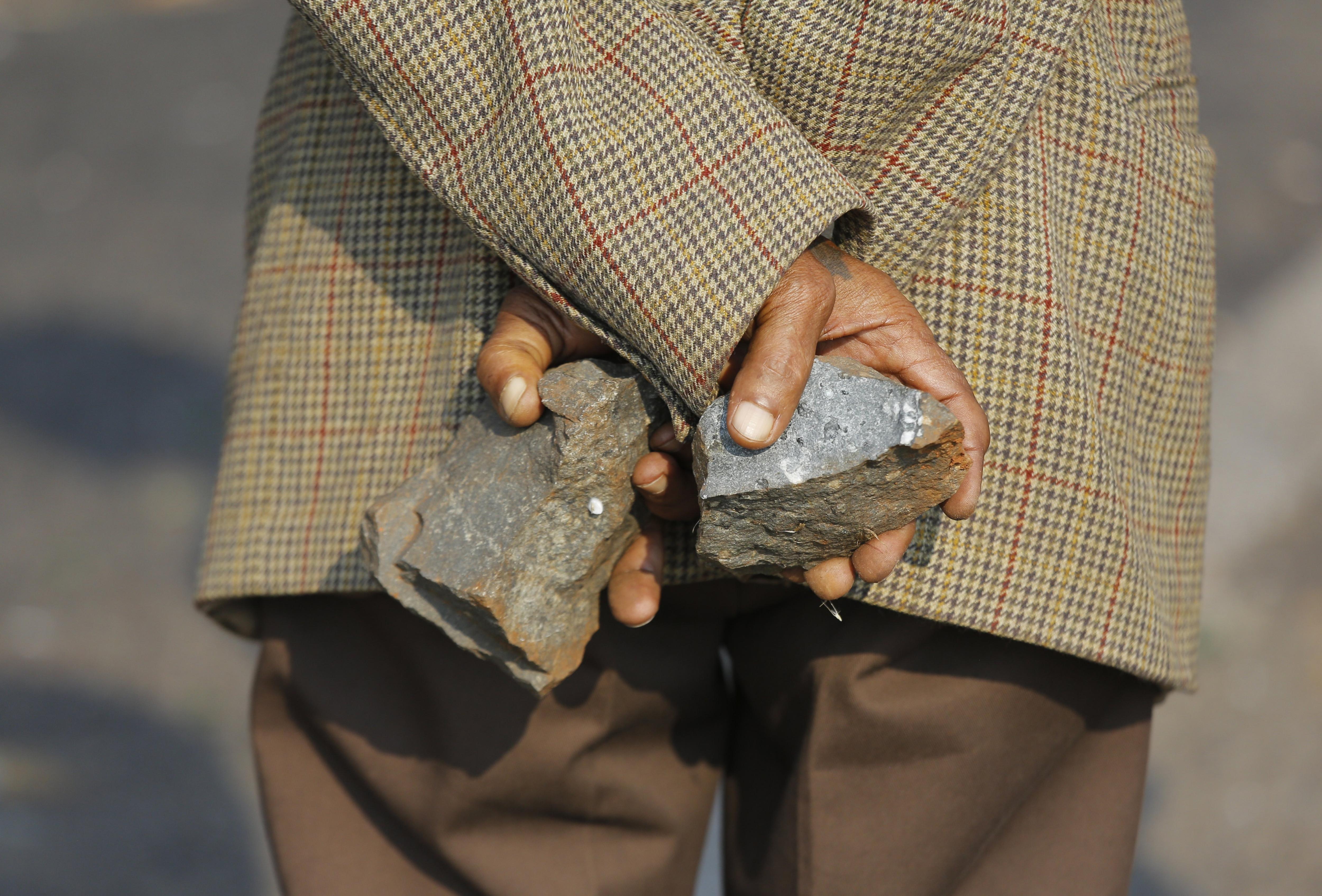 Un manifestant s'amaga unes pedres darrera de l'esquena durant una protesta per exigir habitatges dignes a Ennerdale, Johannesburg (Sud-àfrica). /KIM LUDBROOK