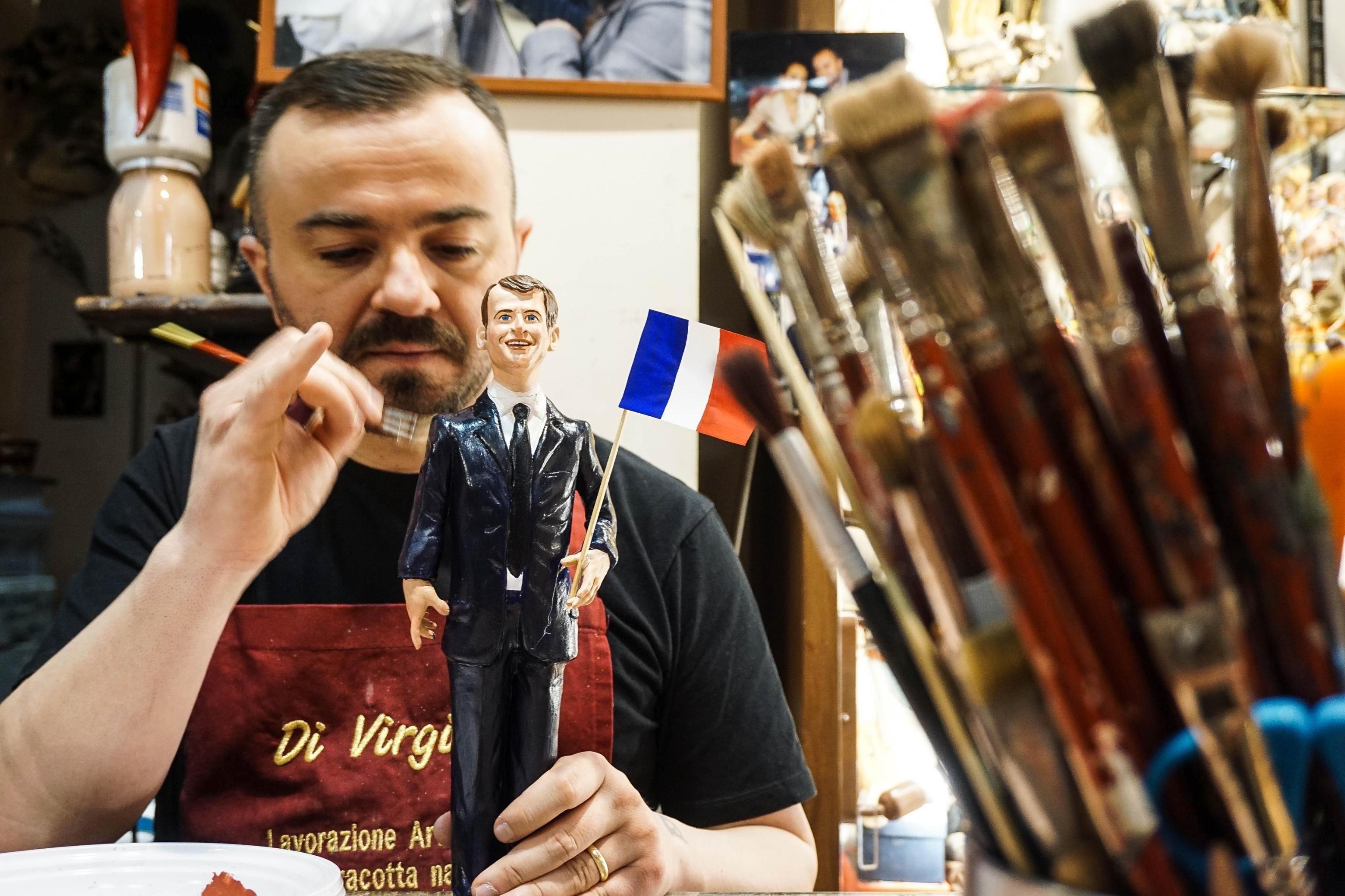 L'artista italià Genny Di Virgilio dóna els últims retocs a una figura del president electe francès, Emmanuel Macron, exposada en un aparador de Nàpols (Itàlia). /CESSÉS ABBATE
