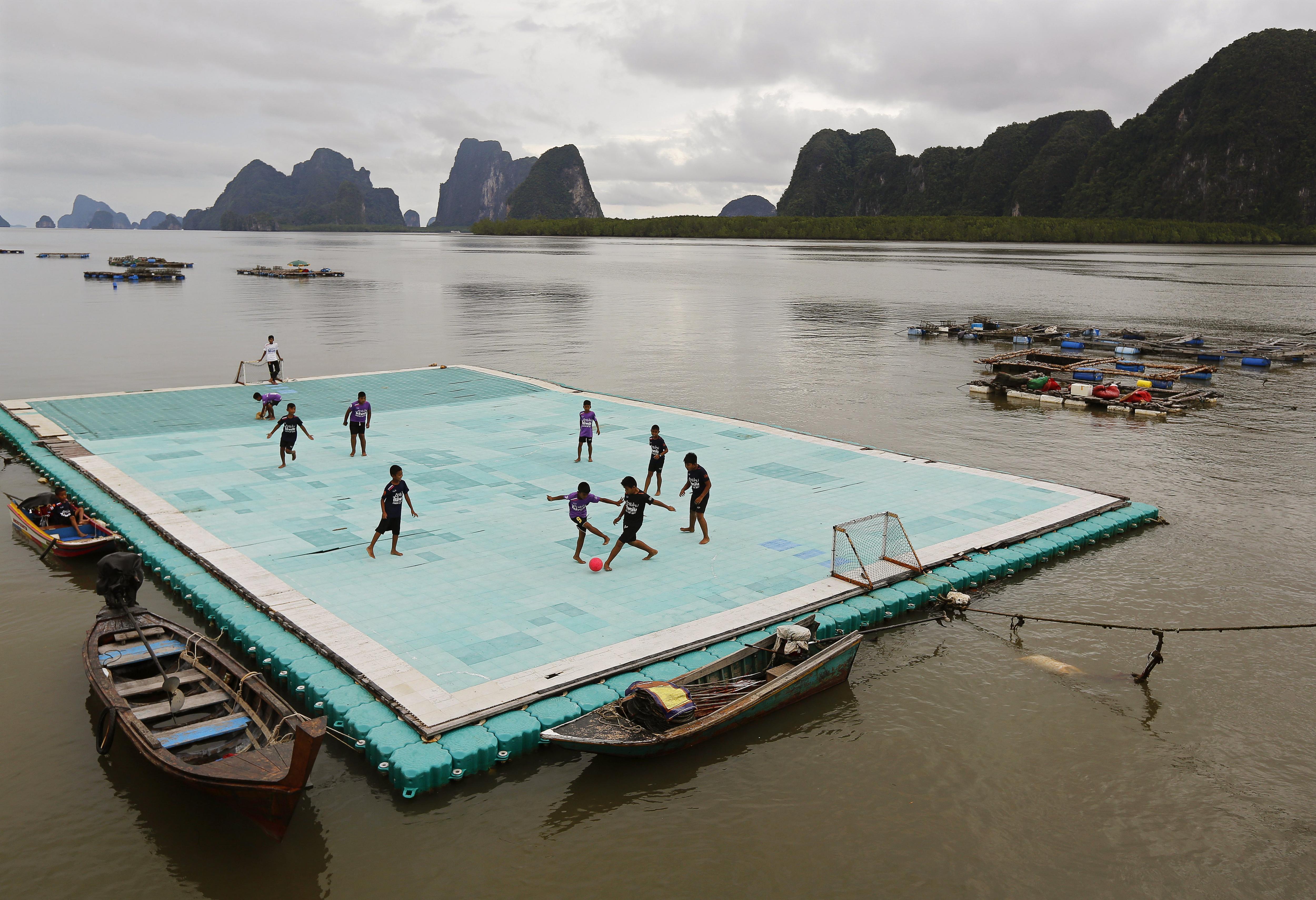 Diversos nins juguen a futbol en una plataforma flotant al poble de Ko Panyi, a la província de Phang Nga, al sud de Tailàndia. /NARONG SANGNAK