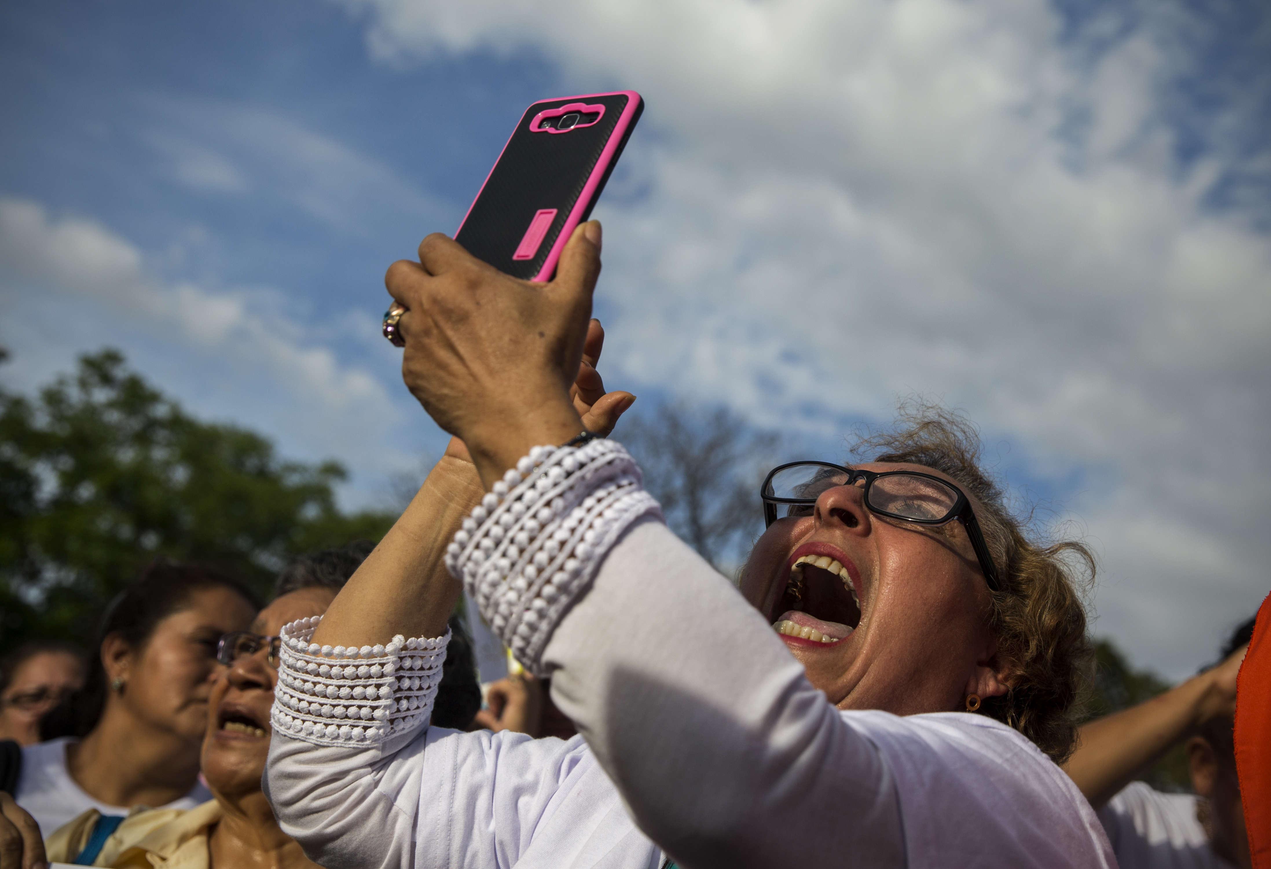 Una dona crida durant el pas d'una rèplica de la verge de Fátima procedent de Guatemala a Managua (Nicaragua). /JORGE TORRES