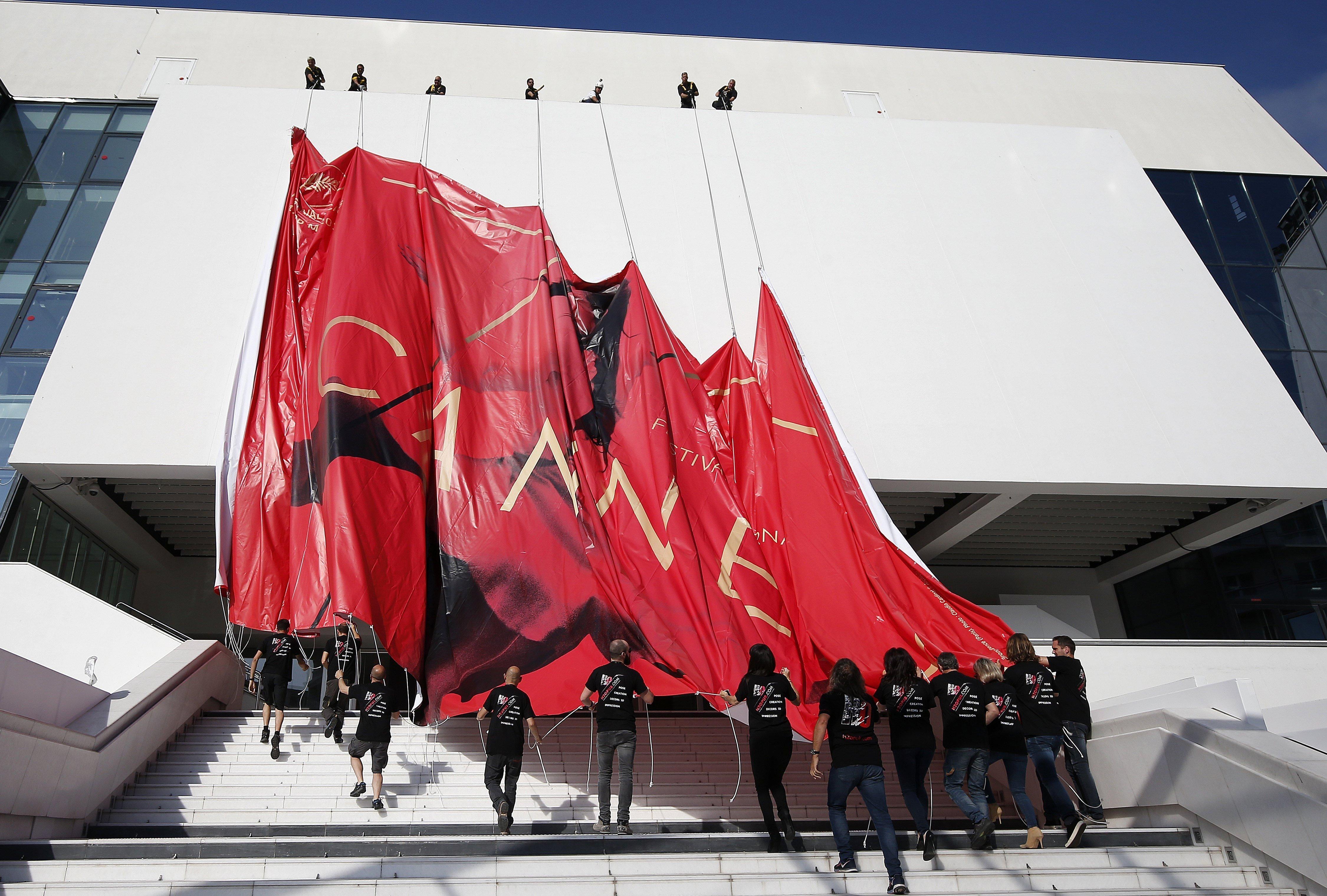 Treballadors col·loquen el pòster oficial del Festival de Cinema de Cannes (França). /SEBASTIEN NOGIER
