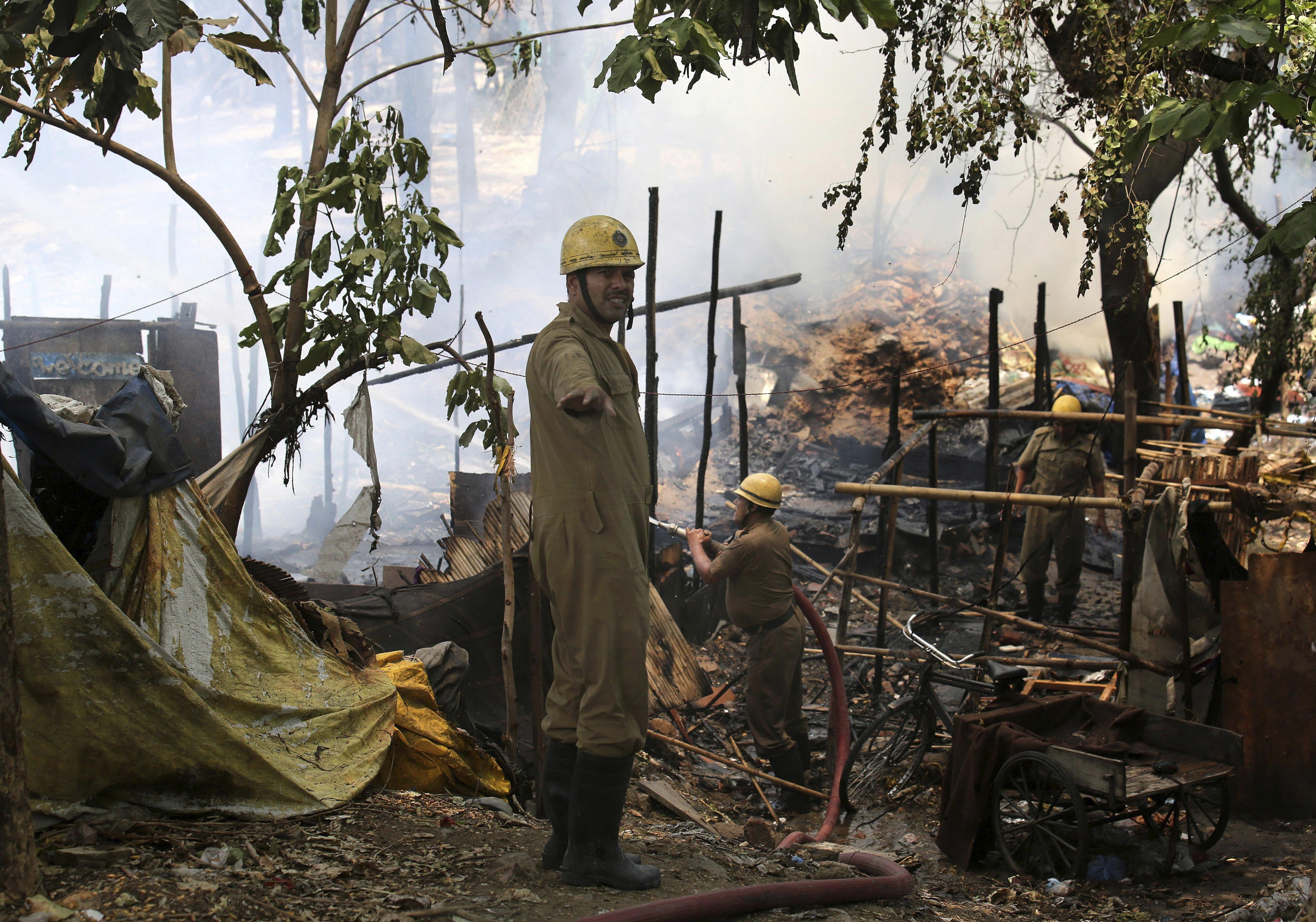 Bombers extingeixen un incendi declarat a un barri de barraques a Nova Delhi (Índia). /RAJAT GUPTA