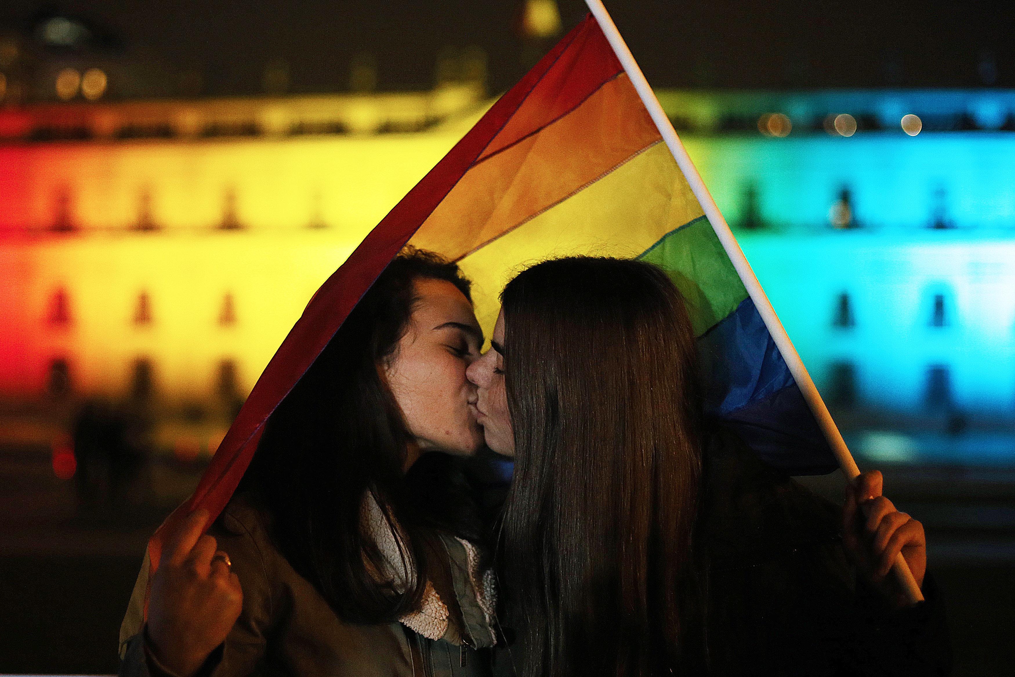 Dues dones es besen davant el Palau de la Moneda, il·luminat amb els colors de l'arc de Sant Martí a Santiago (Xile). /MARIO RUIZ