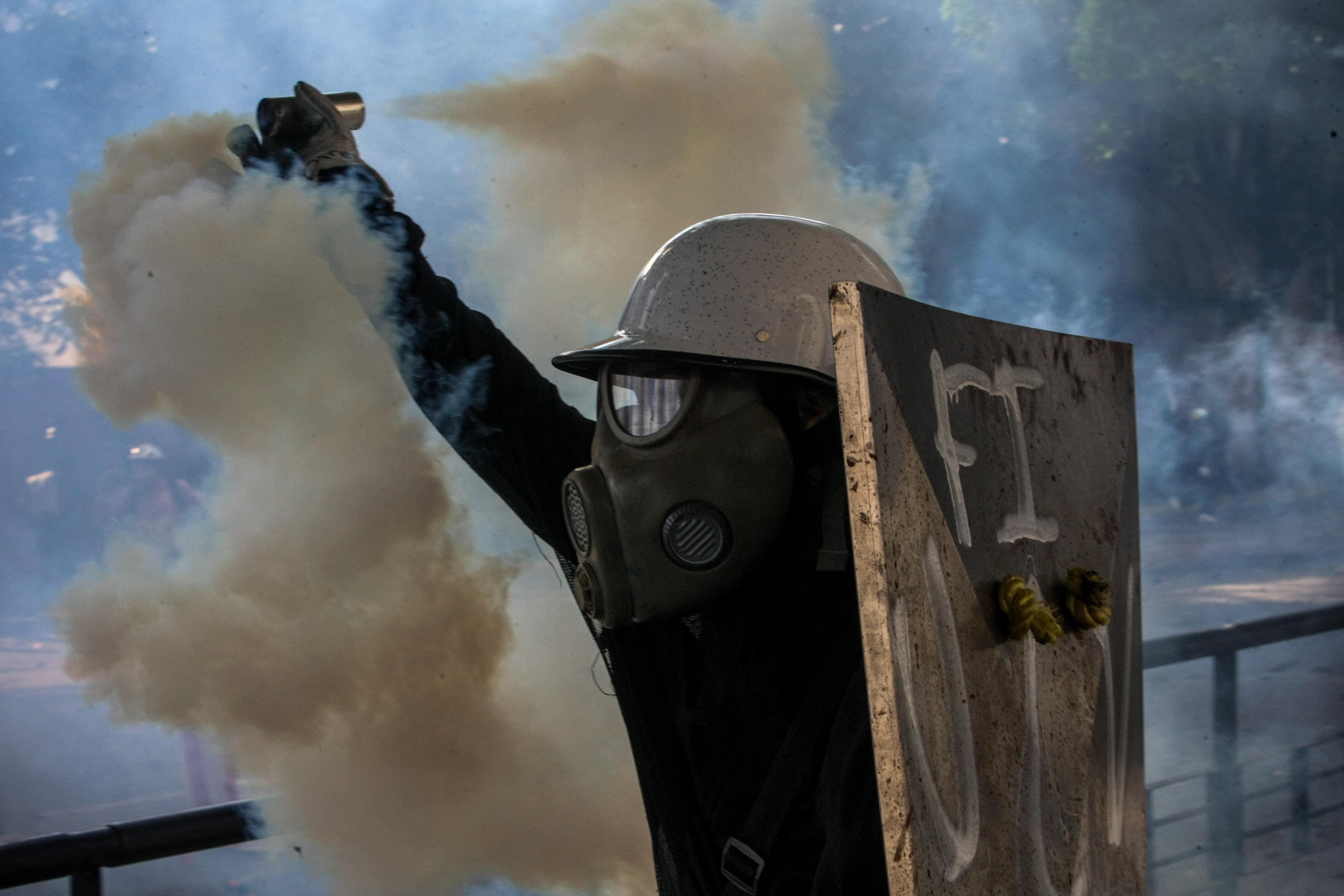 Un grup de manifestants s'enfronta a la Guàrdia Nacional Bolivariana (GNB) durant una marxa antigovernamental a Caracas (Veneçuela). /CRISTIAN HERNÁNDEZ