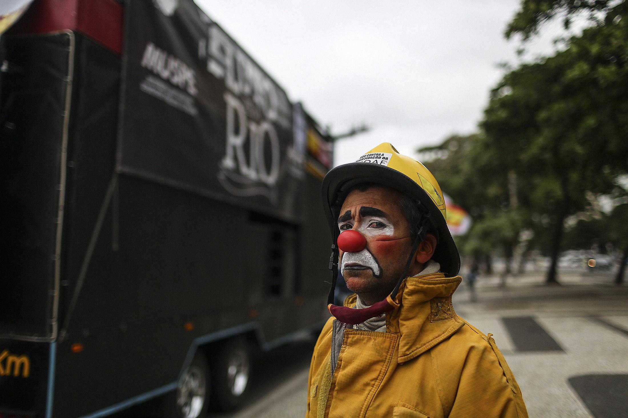 Un home vestit de bomber pallasso participa en una protesta a la platja de Copacabana, Rio de Janeiro (Brasil), contra el govern de Michel Temer. /ANTONIO LACERDA