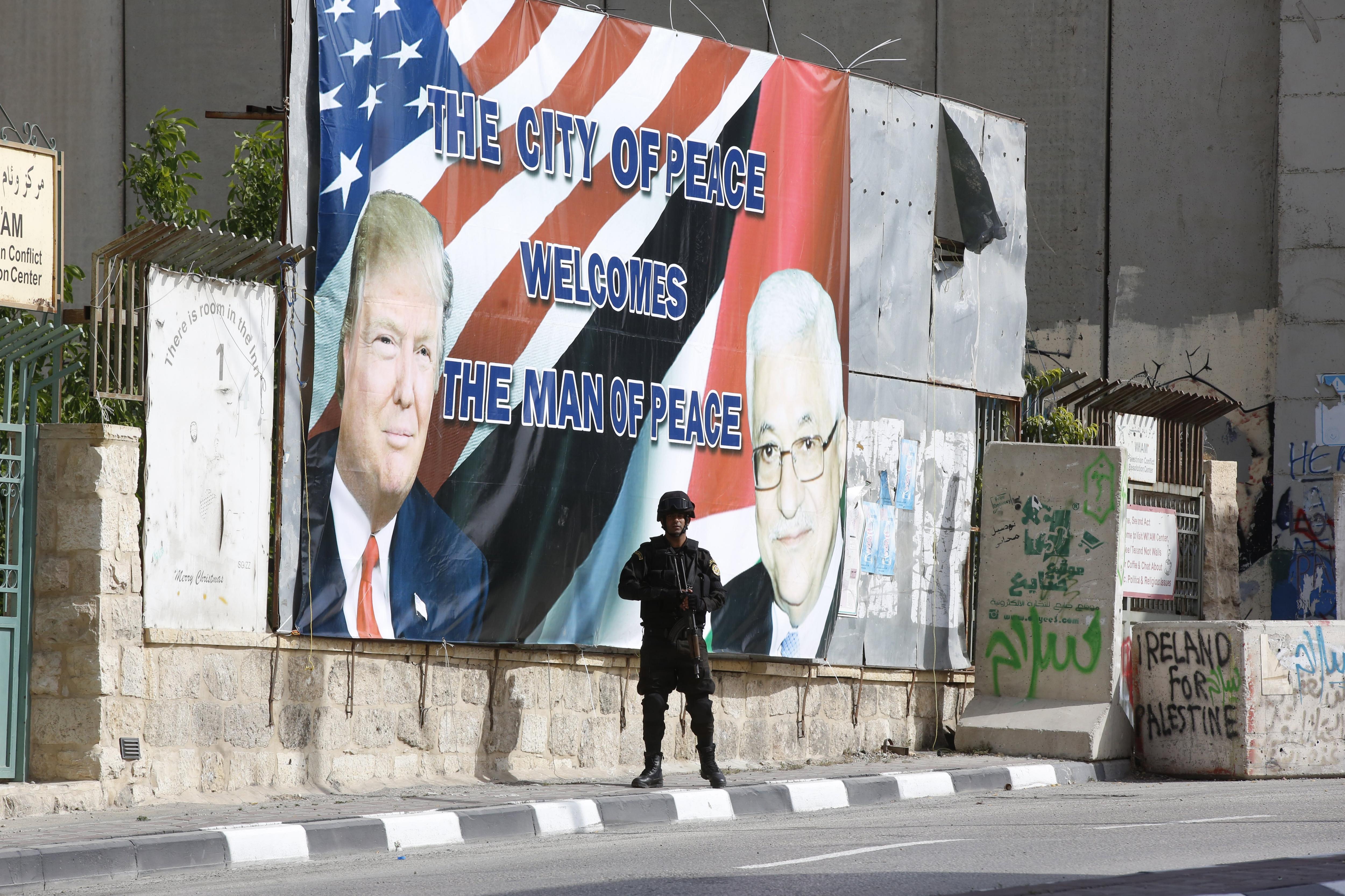 Un soldat palestí fa guàrdia al costat d'una pancarta en la qual es pot llegir 'La ciutat de la pau dóna la benvinguda a l'home de la pau' en la qual apareixen les fotografies del president palestí, Mahmud Abás, i del president dels EUA, Donald Trump, a Palestina. / ALAA BADARNEH