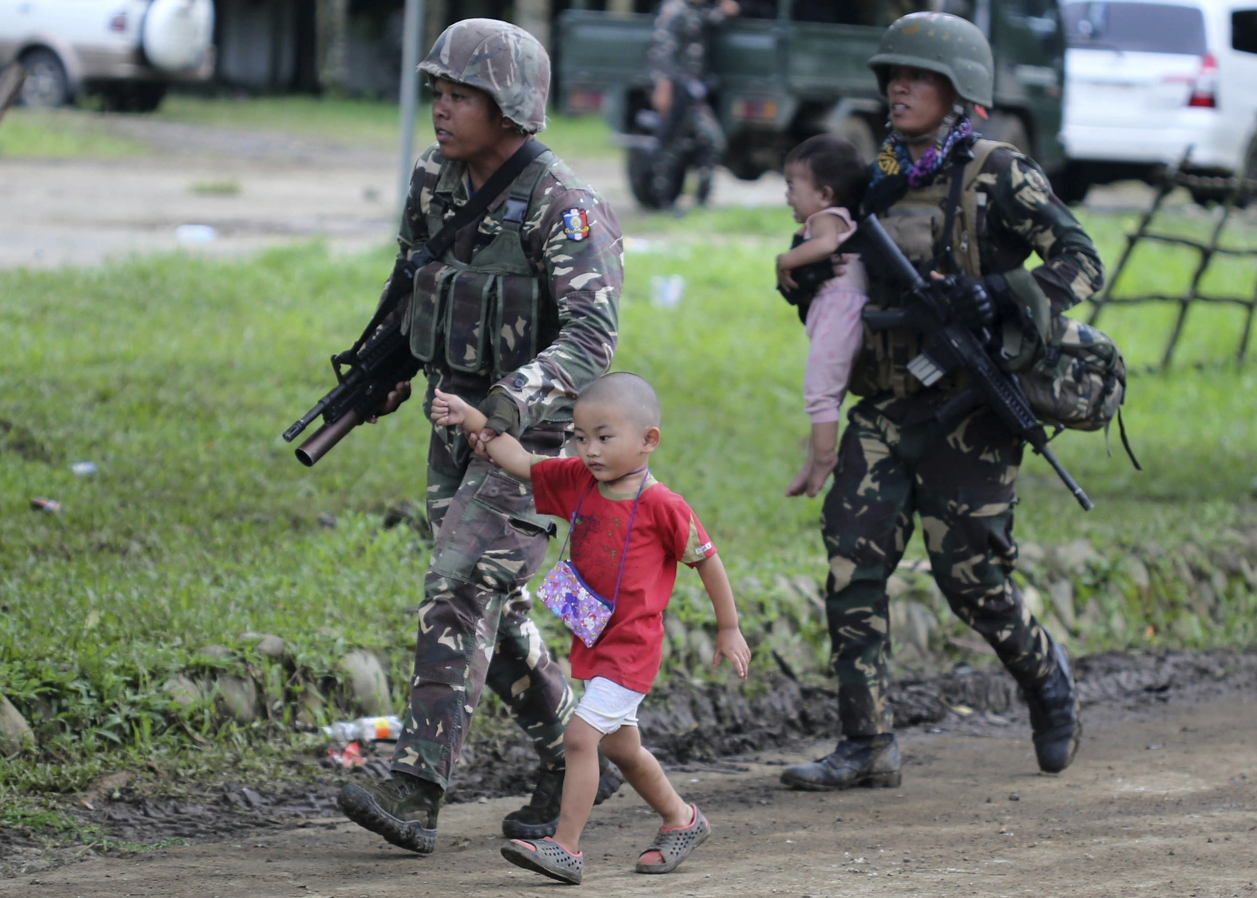 Soldats filipins protegeixen dos nins després dels enfrontaments a la ciutat de Marawi, a Filipines. /LINUS G. ESCANDOR II
