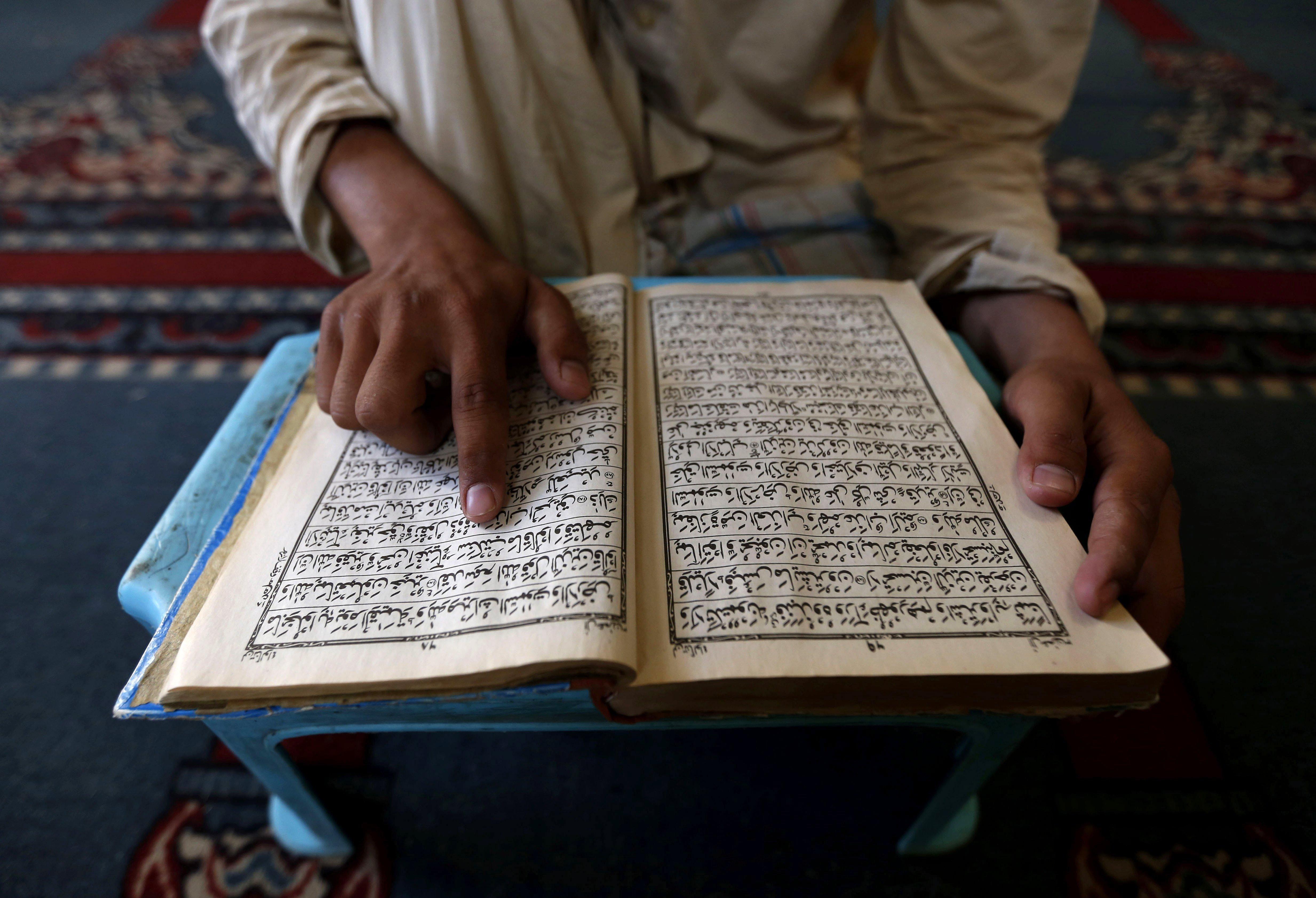 Un jove llegeix l'Alcorà en una mesquita durant la celebració del mes del ramadà a Peshawar (Pakistan). /BILAWAL ARBAB