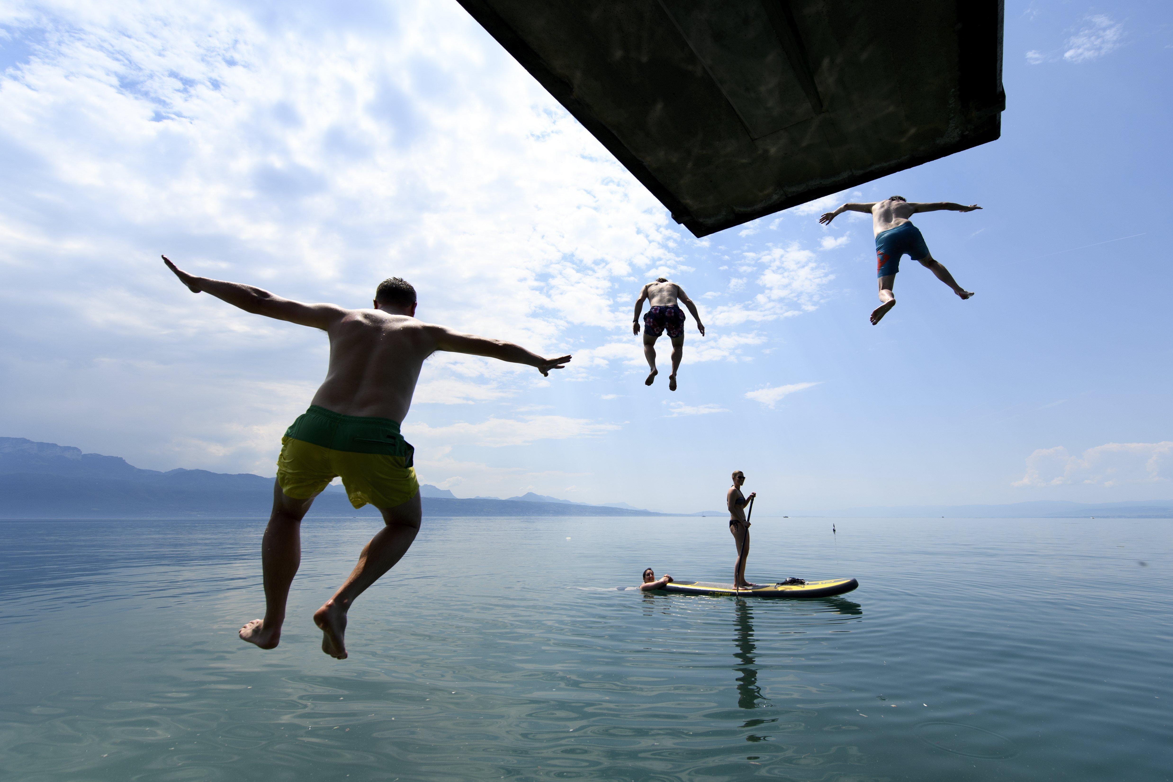 Diverses persones gaudeixen del sol i del bon temps en el llac de Lemán davant els Alps, entre Suïssa i França (Suïssa). /LAURENT GILLIERON