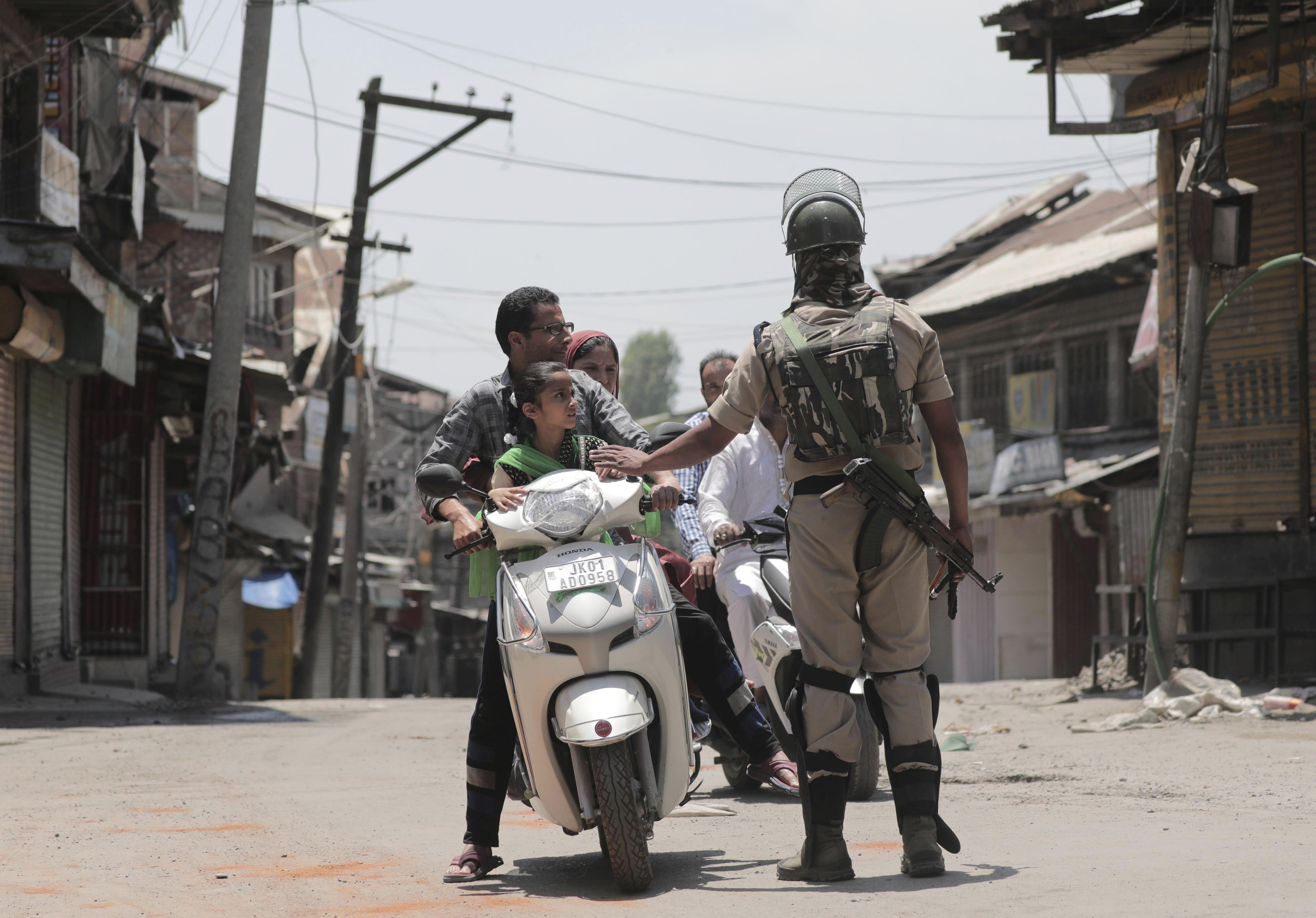 Un paramilitar indi atura una motocicleta durant un toc de queda al centre de Srinagar, Índia. /FAROOQ KHAN