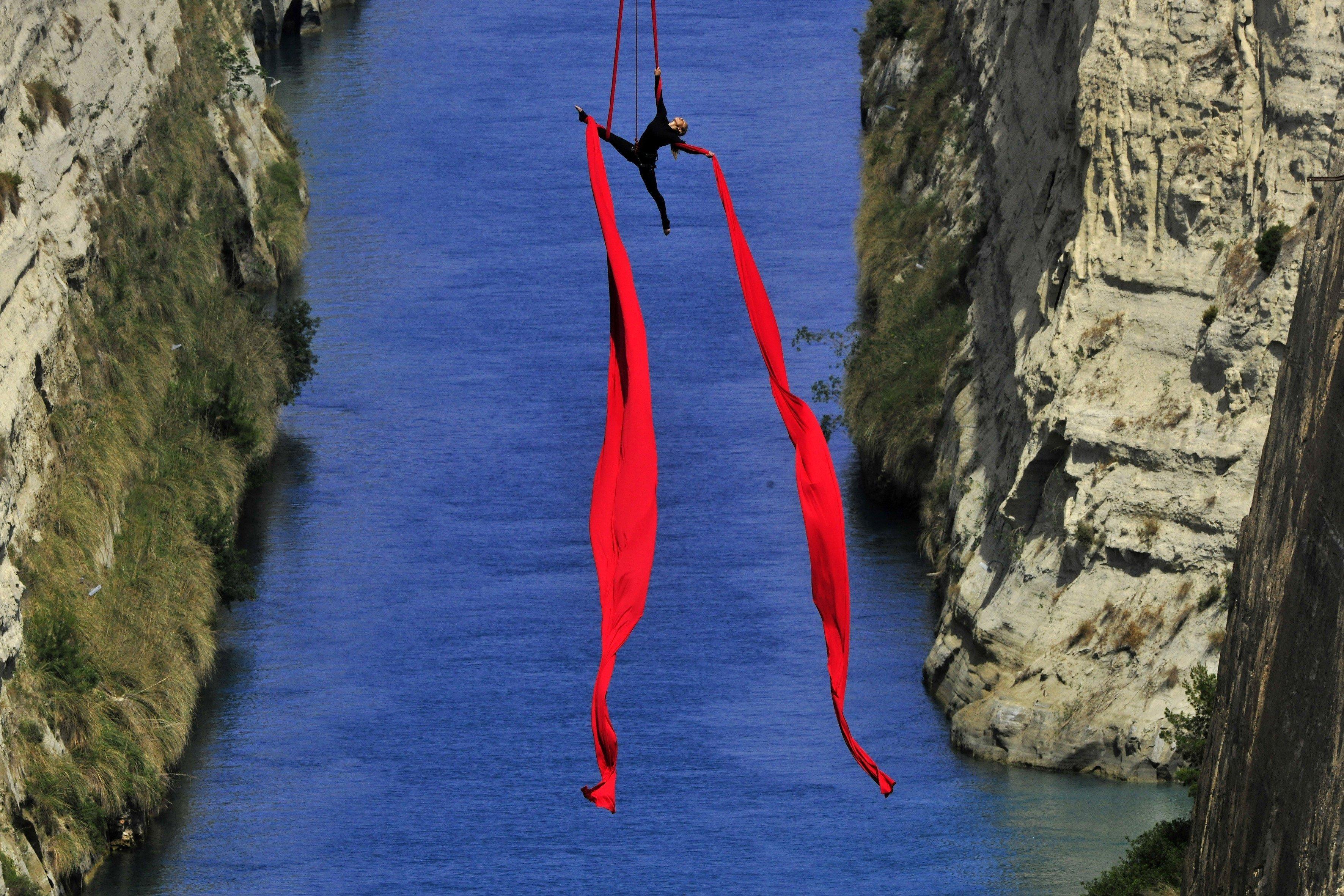 La ballarina i acrobáta grega Katerina Soldatou balla suspesa per dos llaços vermells sobre el canal de Corinto durant la presentació del seu espectacle 'Greece Has Soul' (lit: Alemanya té ànima) a Grècia. /VASSILIS PSOMAS