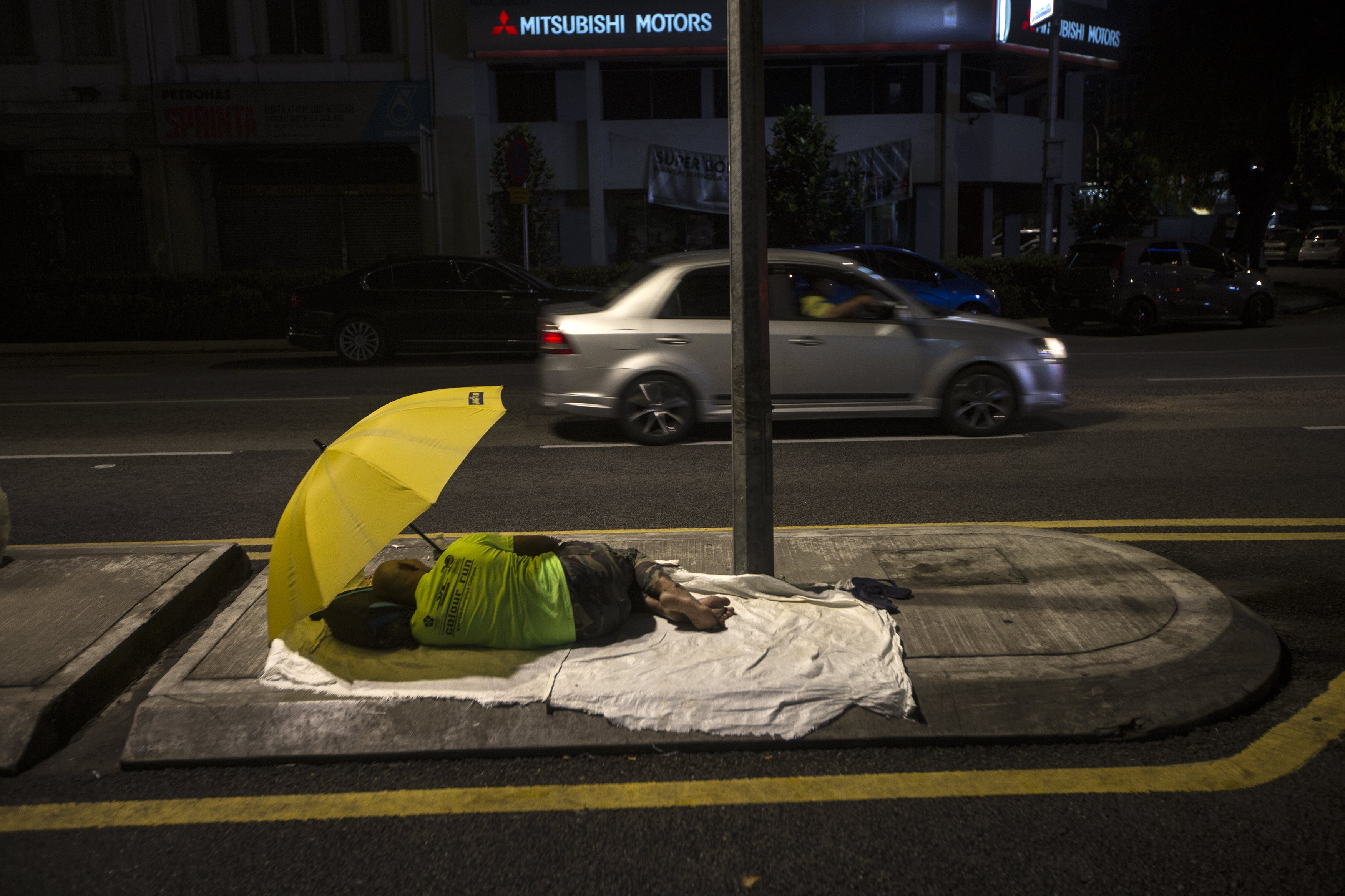 Una persona sense sostre dorm al carrer mentre espera la distribució del menjar sahur durant el mes sagrat del dejuni del Ramadà a Kuala Lumpur (Malàisia). /AHMAD YUSNI