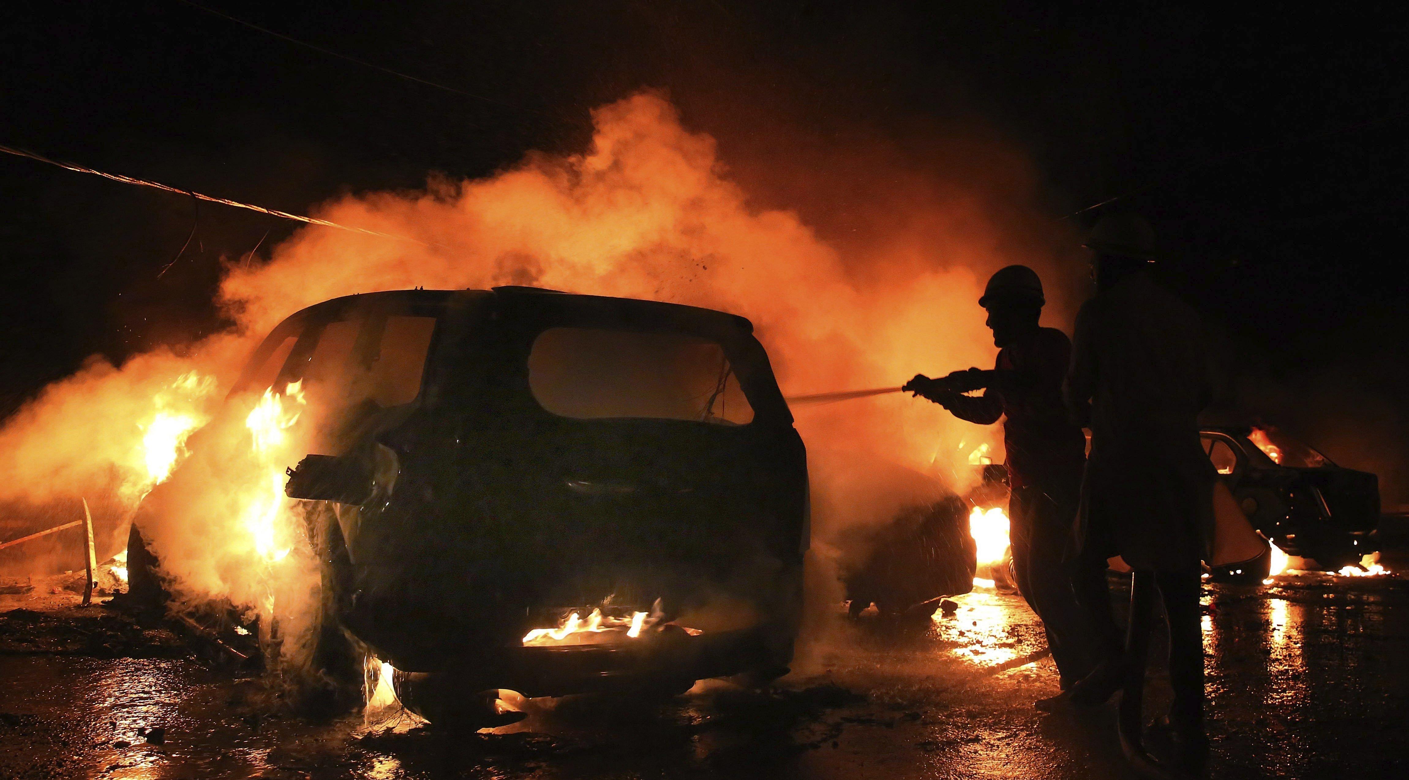 Bombers tracten d'extingir les flames que emboliquen un cotxe durant els disturbis entre membres de les comunitats musulmana i hindú a Bhopal, Índia. /SANJEEV GUPTA