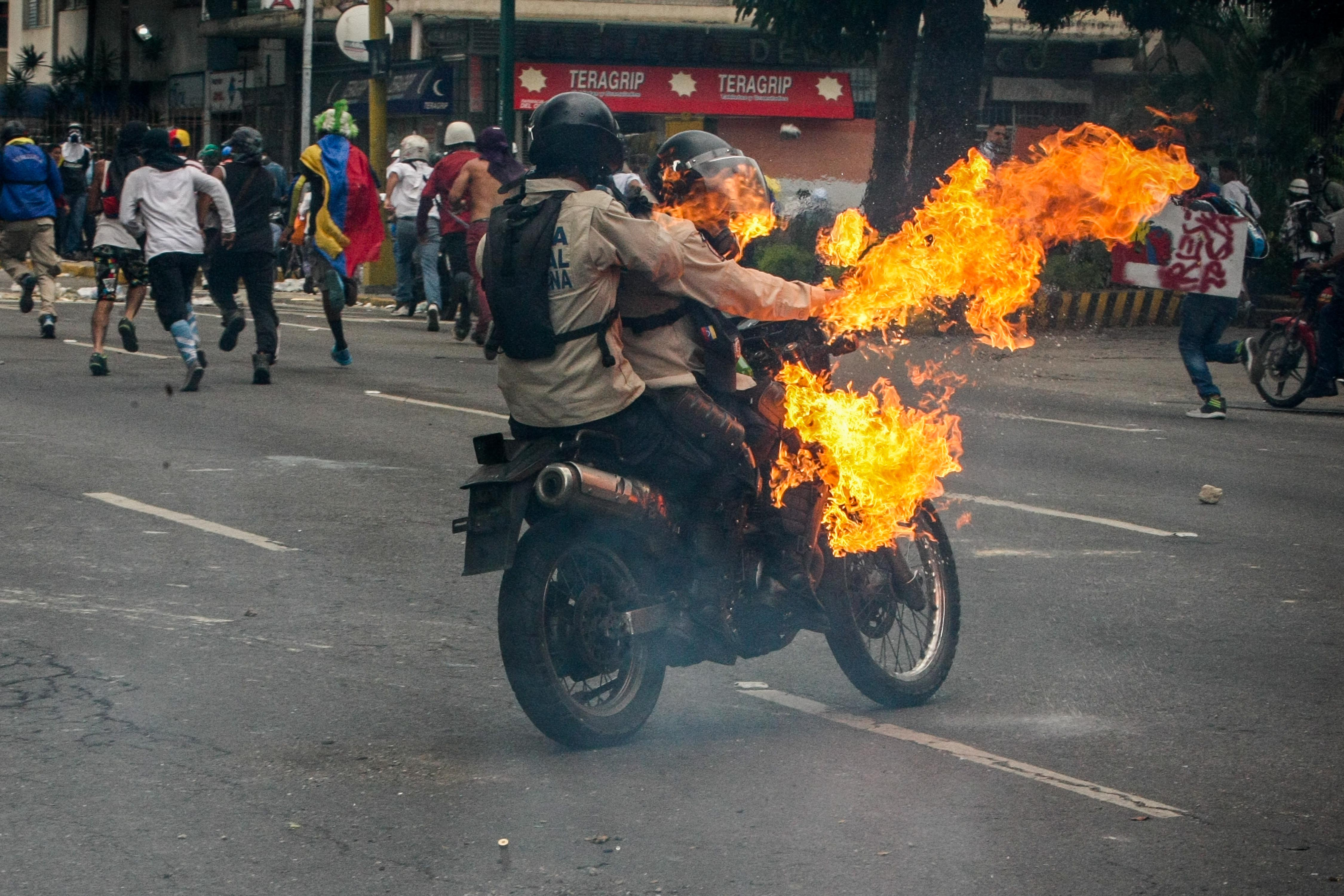 Efectius de la Policia Nacional Bolivariana són atrapats per una bomba Molotov, durant una protesta a Caracas, Veneçuela. /CRISTIAN HERNÁNDEZ