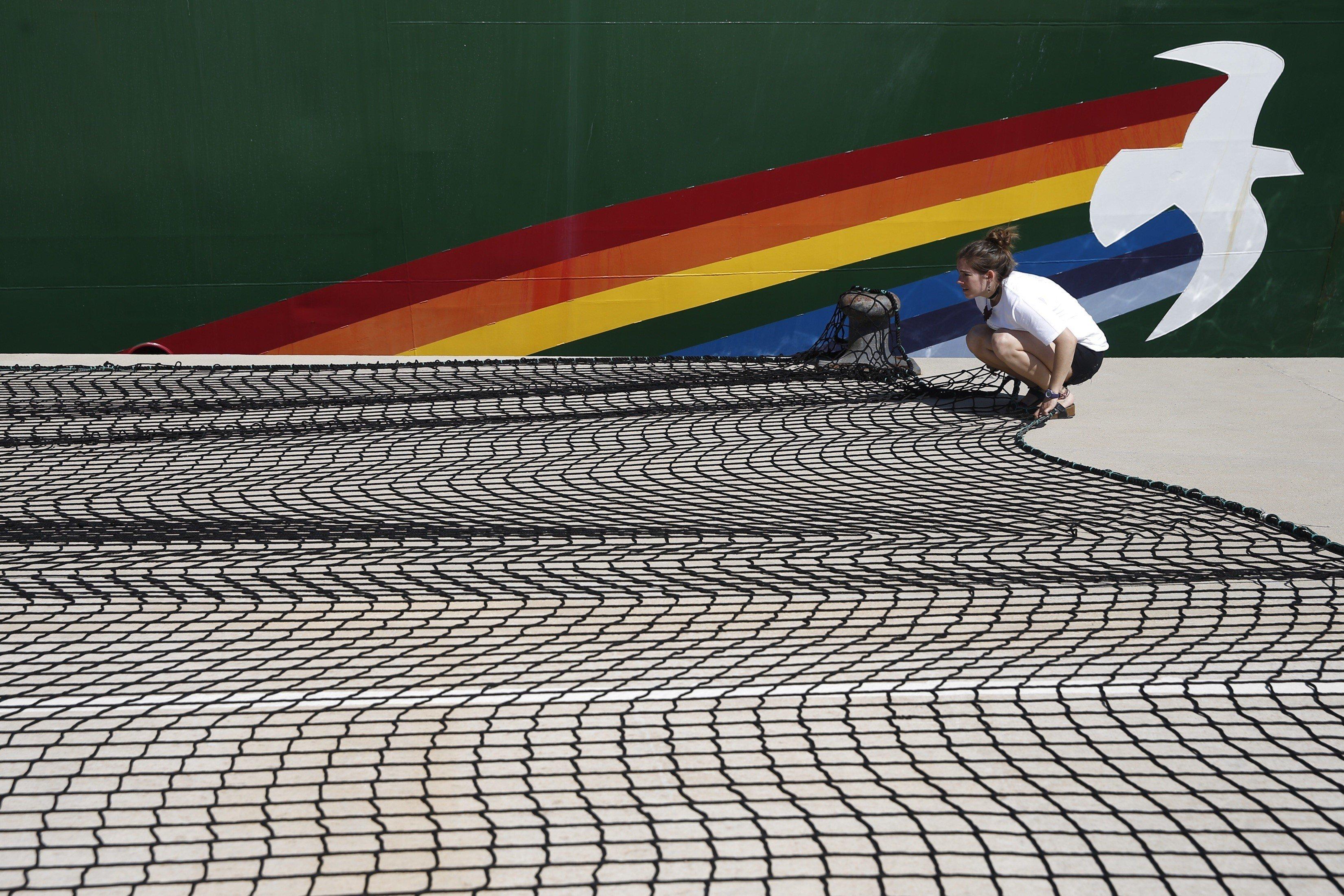 Un membre de l'organització ecologista Greenpeace prepara una xarxa al costat del buc 'Rainbow Warrior', moments abans de presentar, amb motiu del Dia dels Oceans, l'informe 'Un Mediterrani ple de plàstic'./Kai Forsterling