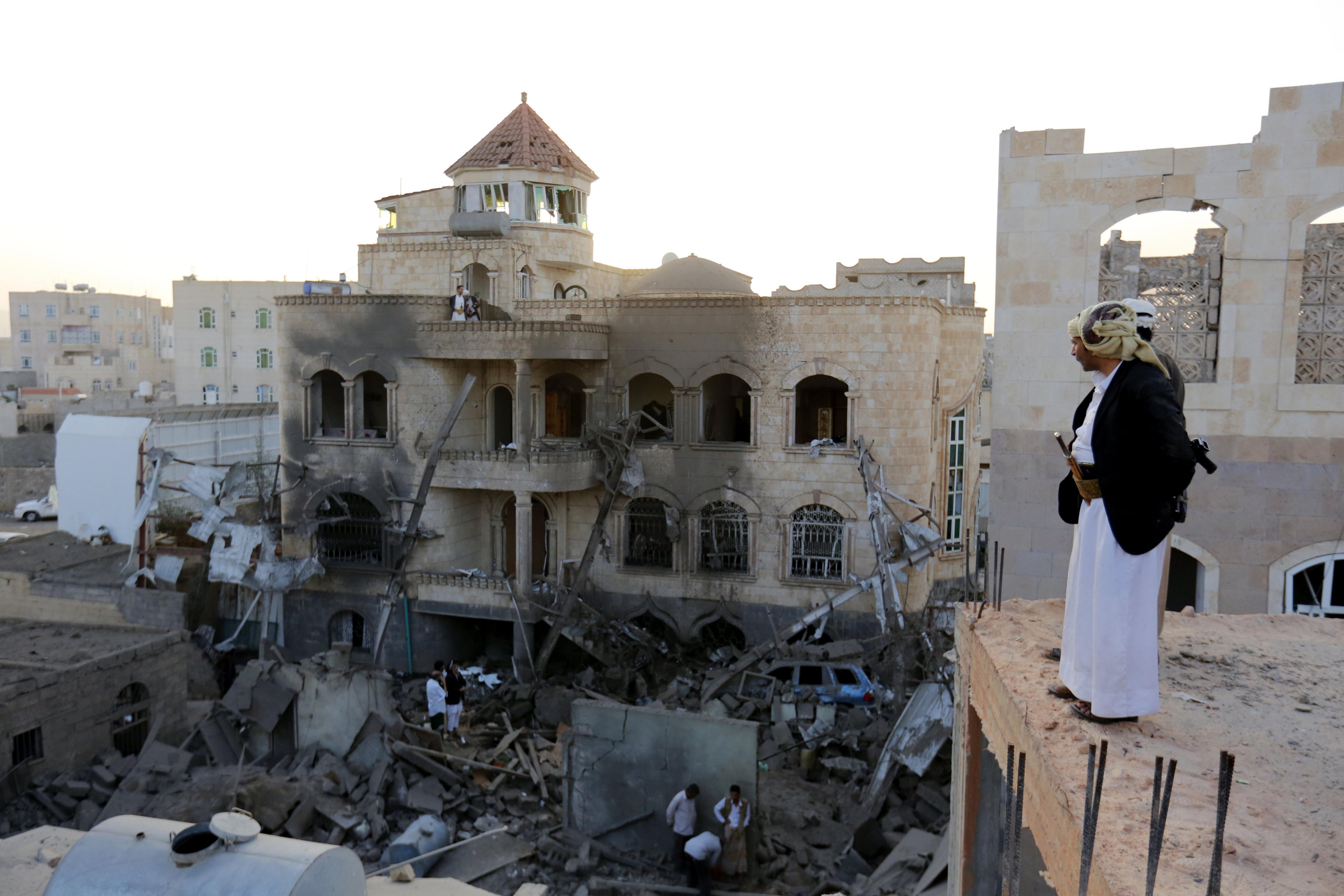 Iemenites observen els danys causats per un suposat atac de la coalició internacional liderada per Aràbia Saudita a un barri de Saná, Iemen. Tres nens i una dona van morir, mentre que altres quatre persones van resultar ferides./Yahya Arhab