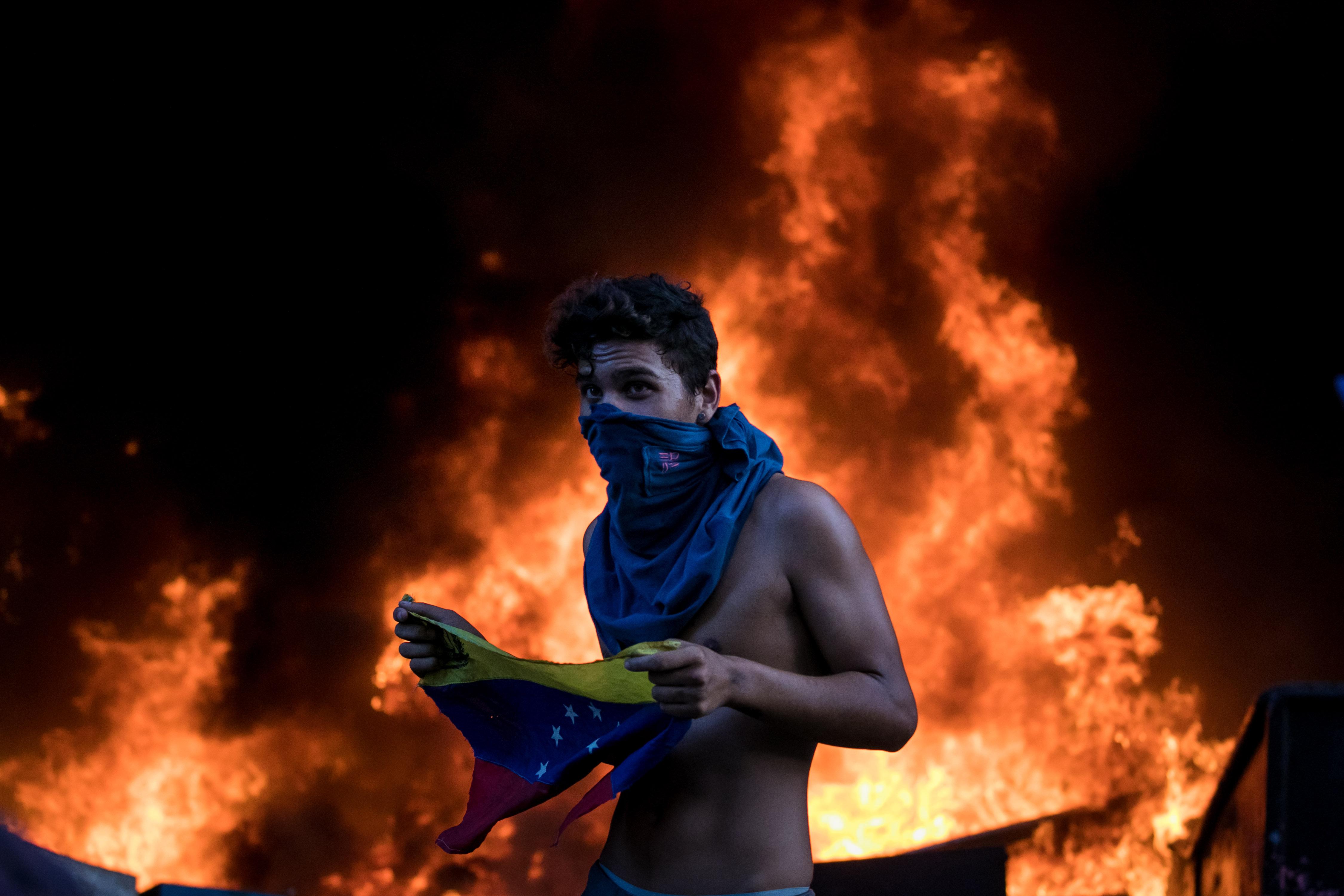 Un manifestant participa en una protesta a Caracas, Veneçuela. Els encaputxats han incendiat la Direcció executiva de la Magistratura del Tribunal Suprem de Veneçuela situada en Chacao, en l'est de Caracas./Miguel Gutiérrez