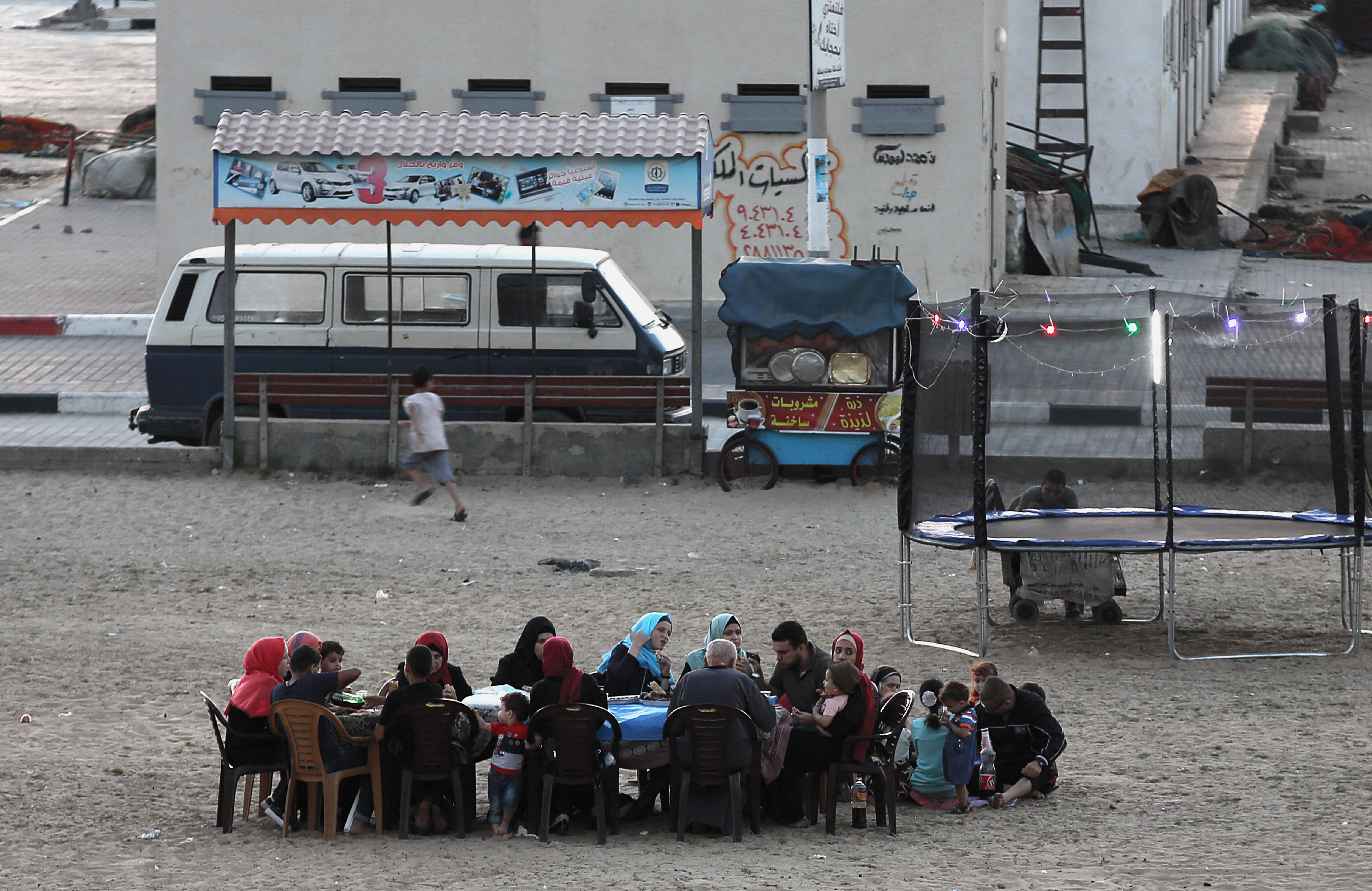 Una família palestina acaba el seu dejuni a la platja durant el Ramadà a la ciutat de Gaza./MOHAMMED SABER