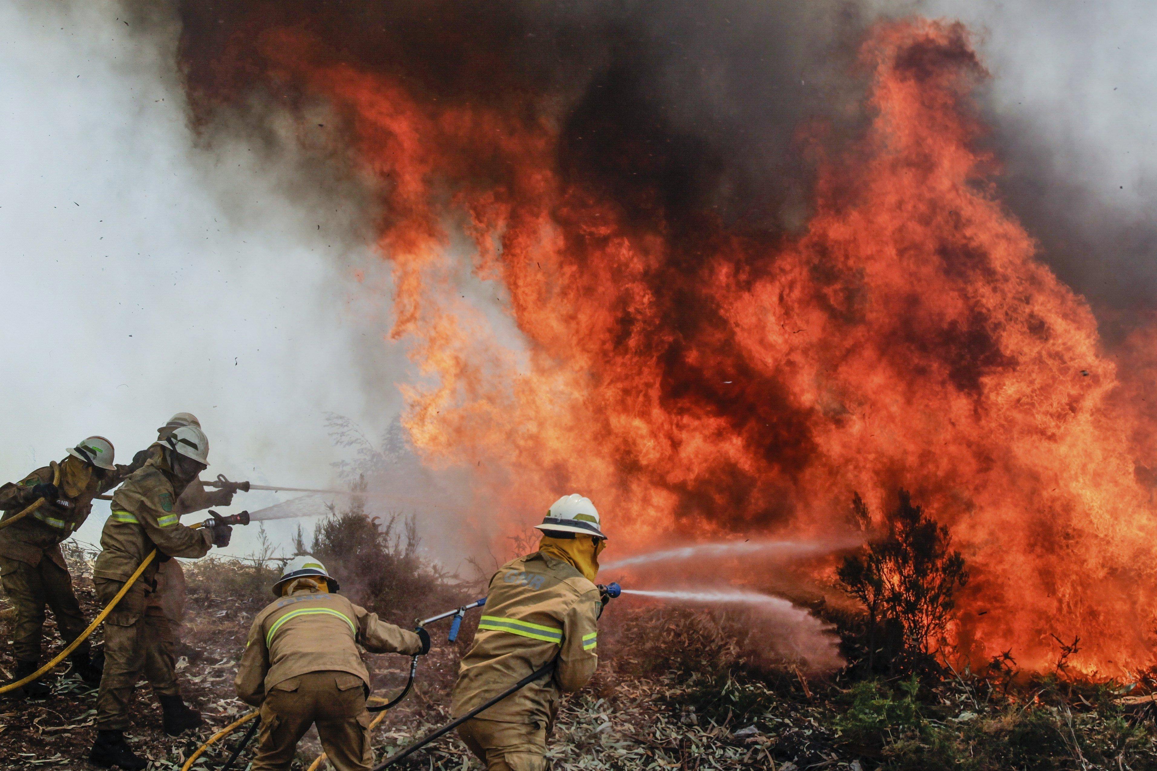 Soldats de la Guàrdia Nacional Republicana portuguesa lluiten contra les flames a Capela Sao Neitel, Alvaiazere (Portugal). /PAULO CUNHA