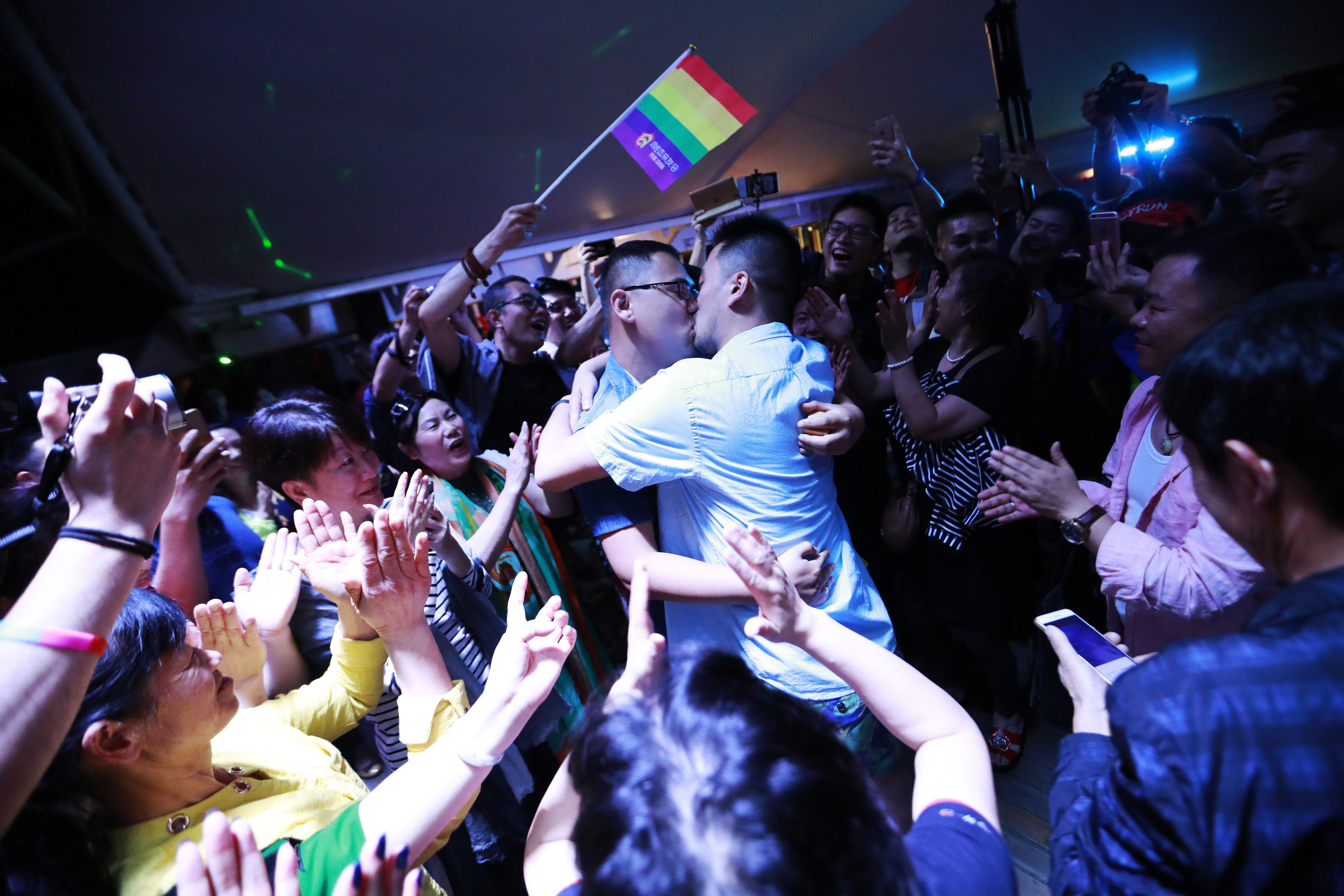 Una parella es besa durant la celebració simbòlica de diverses noces homosexuals en un creuer organitzat per l'organització xinesa de Pares i Amics de Lesbianes i Gais (PFLAG) que es dirigeix a Sasebo, el Japó. /HOW HWEE YOUNG