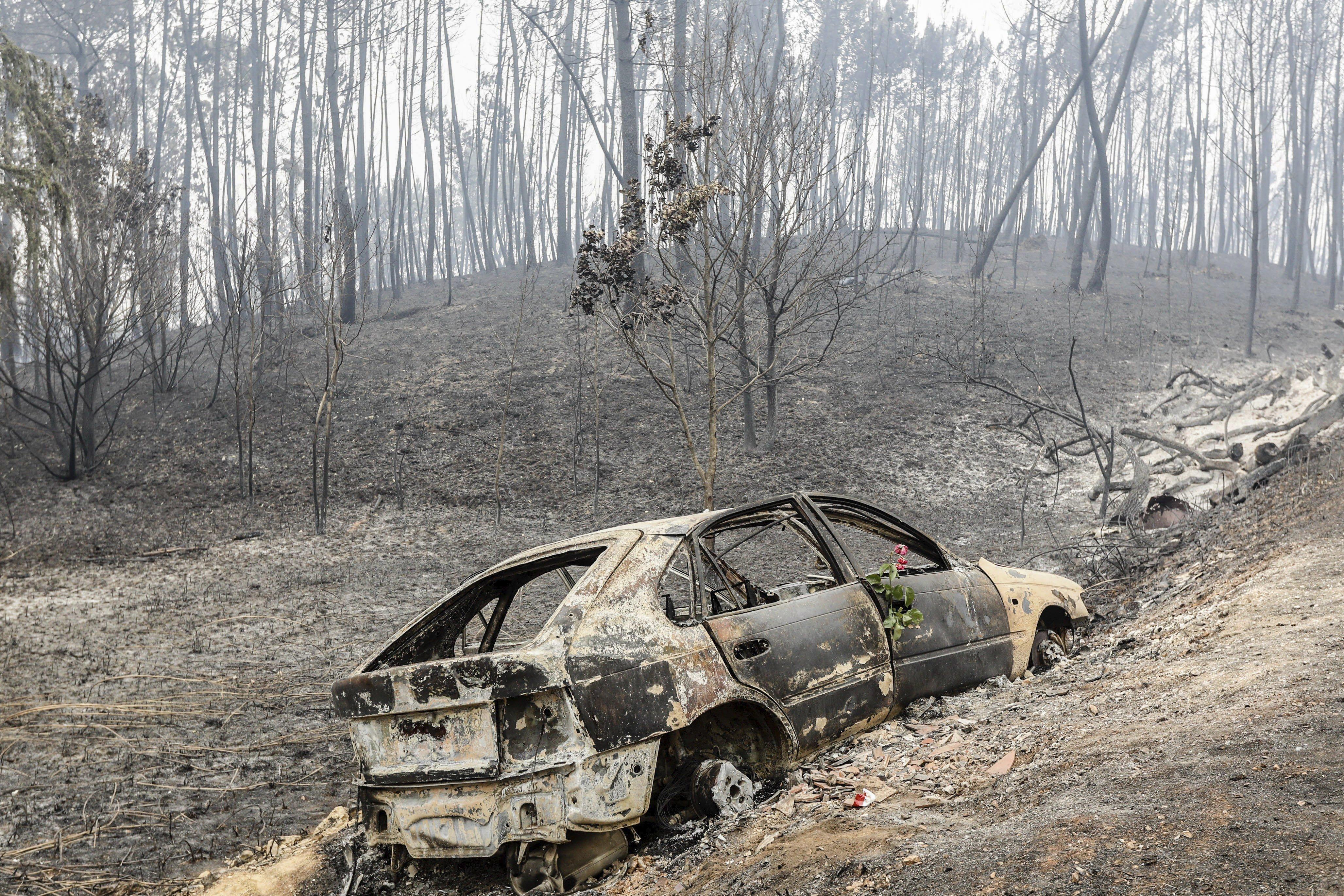 Un vehicle destrossat pel foc a Nodeirinho, prop de Pedrógão Gran (Portugal). /ANTONIO COTRIM