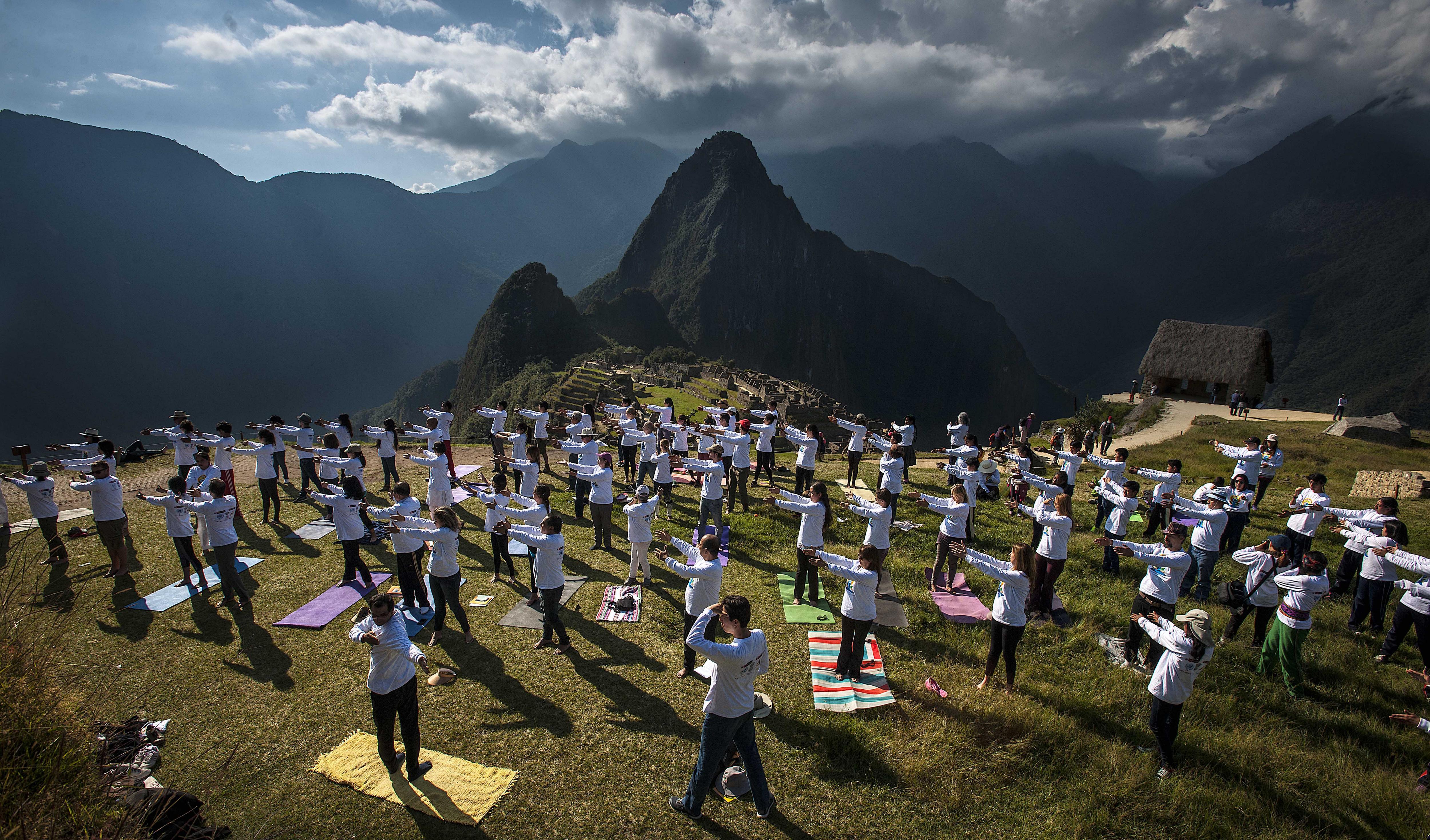Centenars de persones practiquen ioga en el cim de la històrica fortalesa del Machu Pichu. /EFE