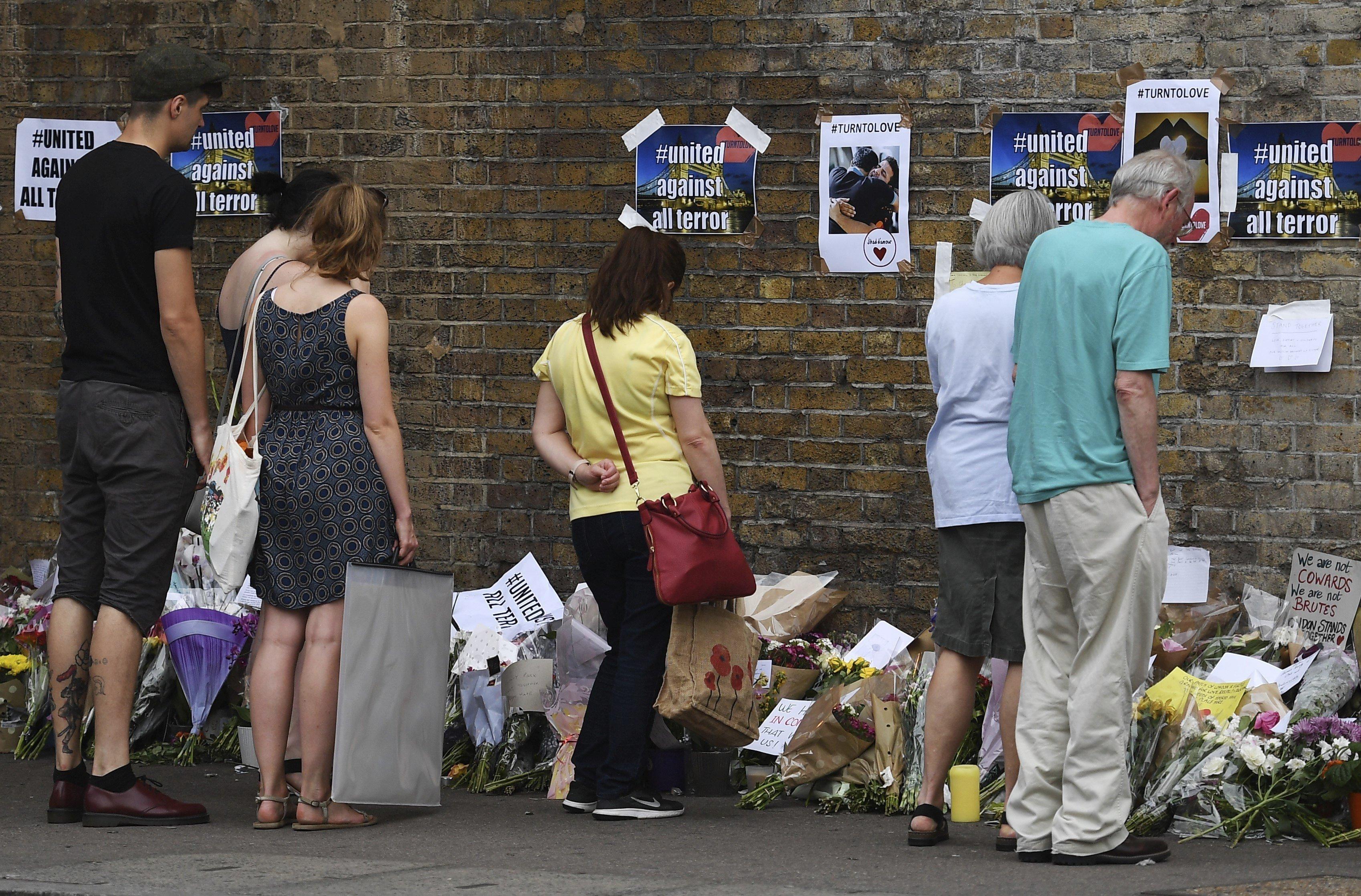Diverses persones observen els missatges de suport, flors i veles en el lloc de l'atac a Finsbury Park, Londres (Regne Unit). /ANDY RAIN