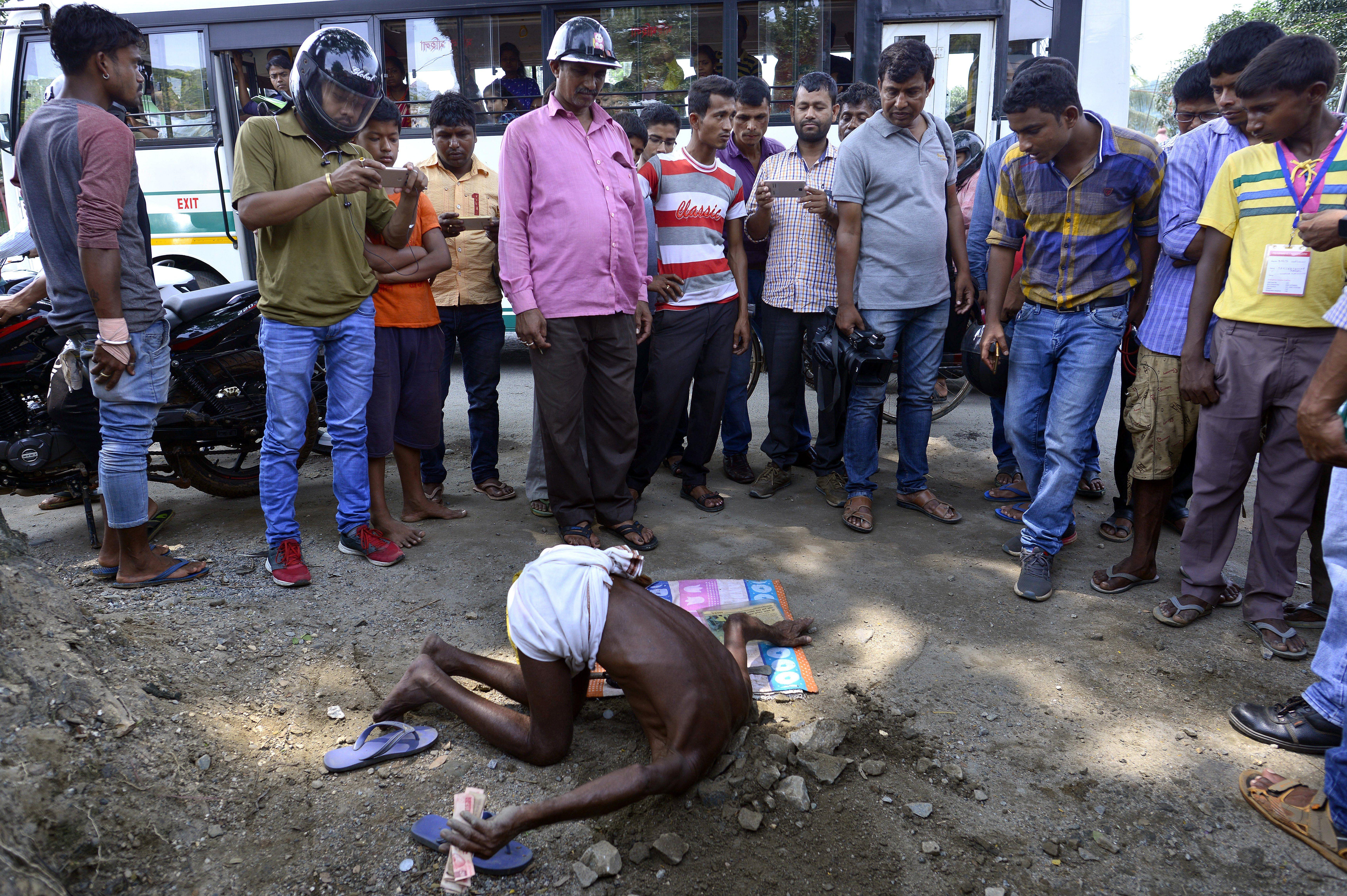 Un religiós indi col·loca el seu cap en un forat sota la terra per demostrar els seus dots místics a Guwahati (Índia). /STR