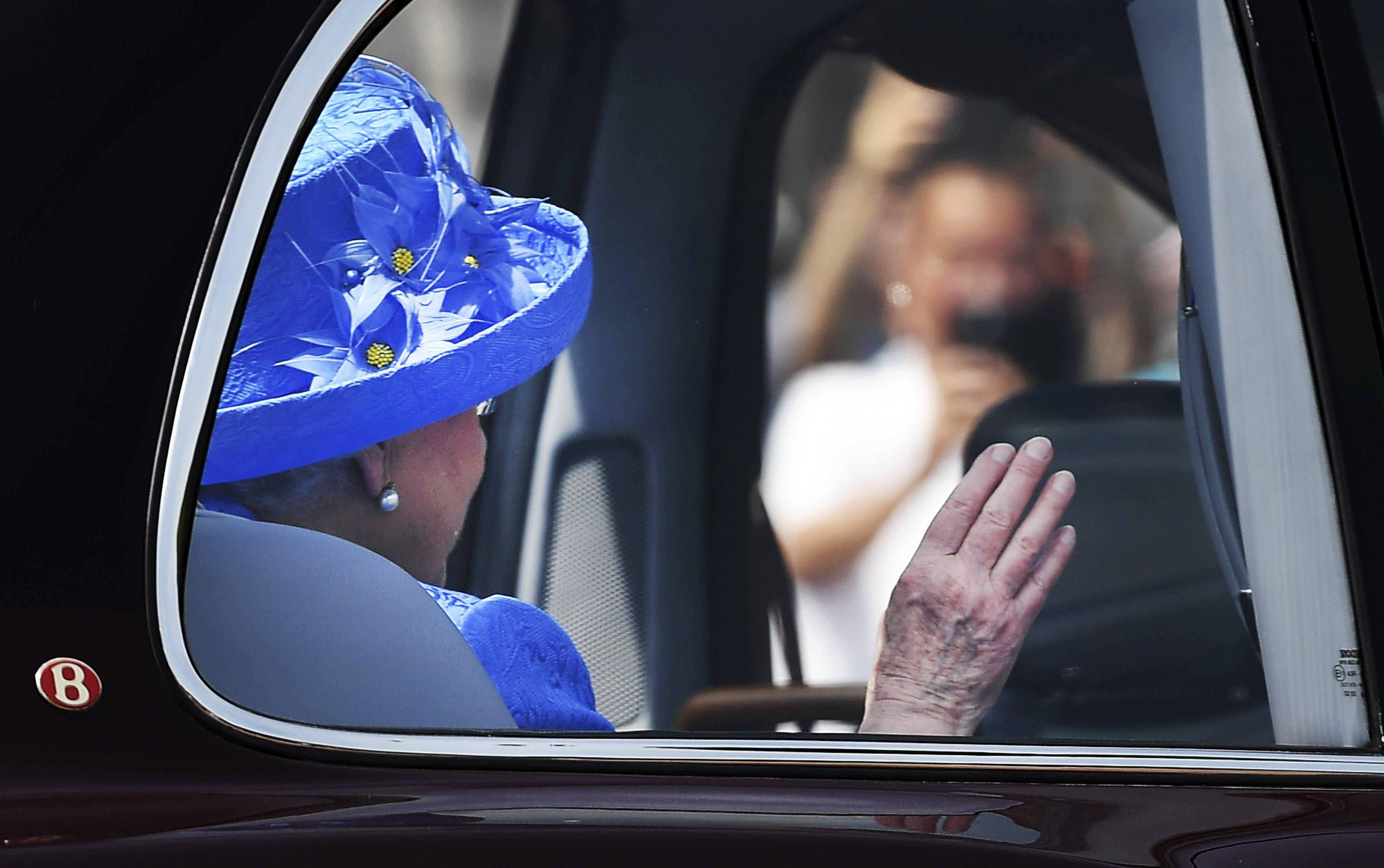 La reina Isabel II saluda en el seu vehicle oficial mentre torna del Parlament, on ha fet la lectura el programa legislatiu del Govern en l'anomenat Discurs de la Reina, a Westminster, Londres (Regne Unit). /ANDY RAIN