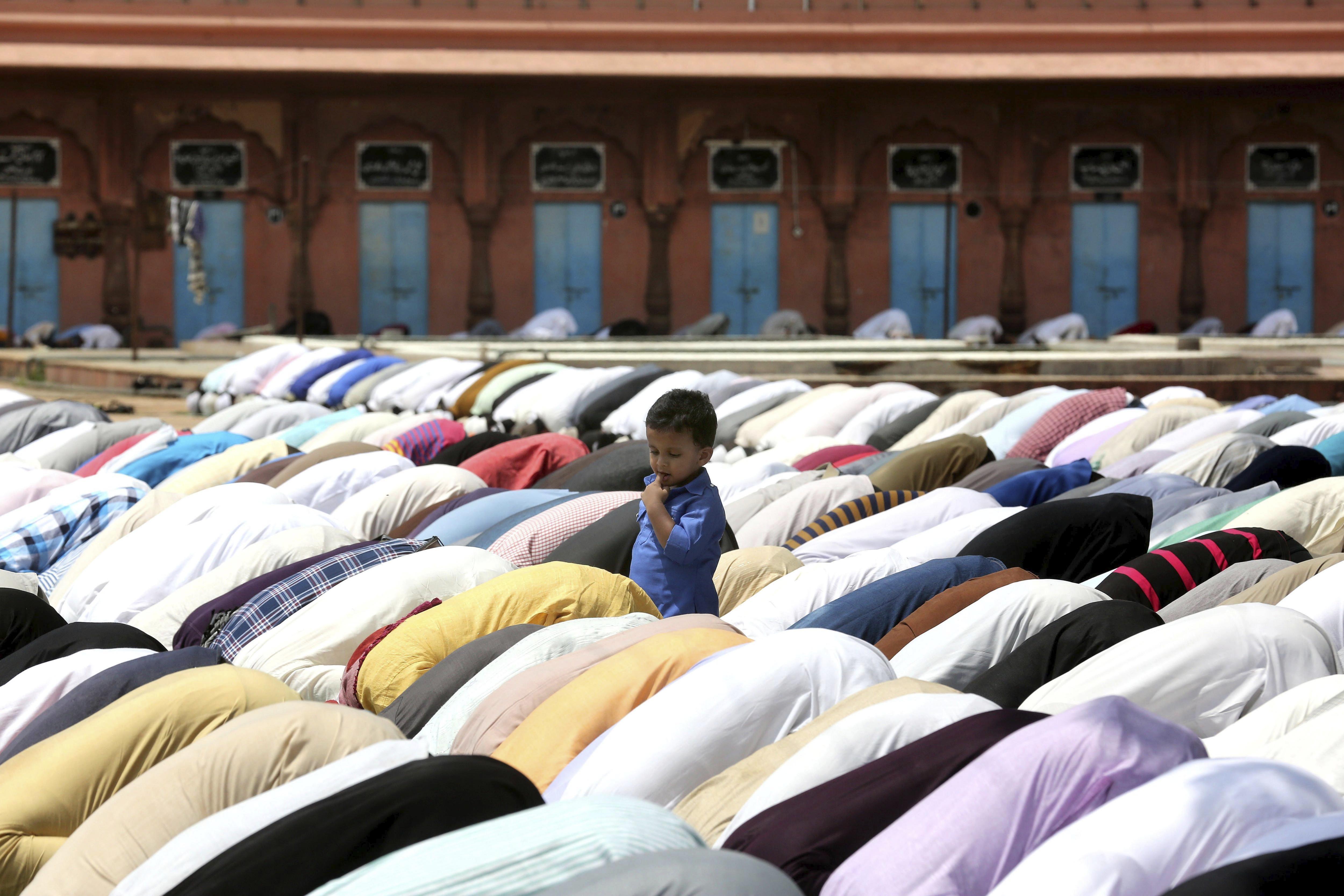 Un nin observa els adults durant el rés en la mesquita Taj-ul-Masajid a Bhopal (Índia), el darrer divendres del mes del Ramadà. /SANJEEV GUPTA