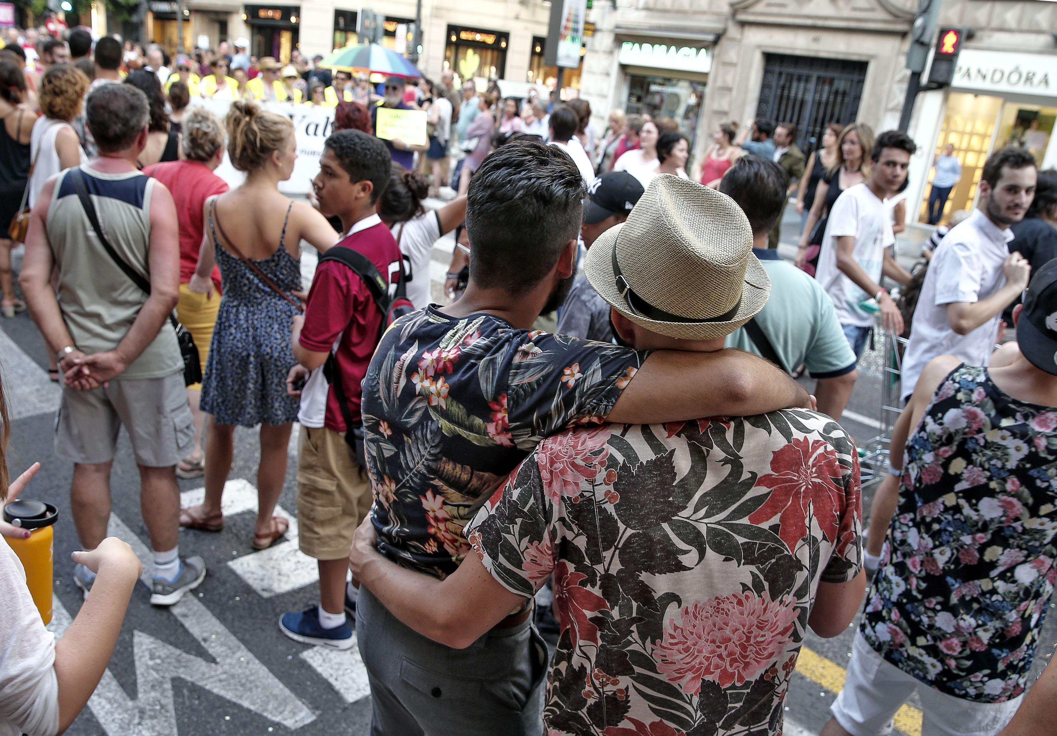 Una parella observa la manifestació de l'Orgull a València. /MANUEL BRUQUE