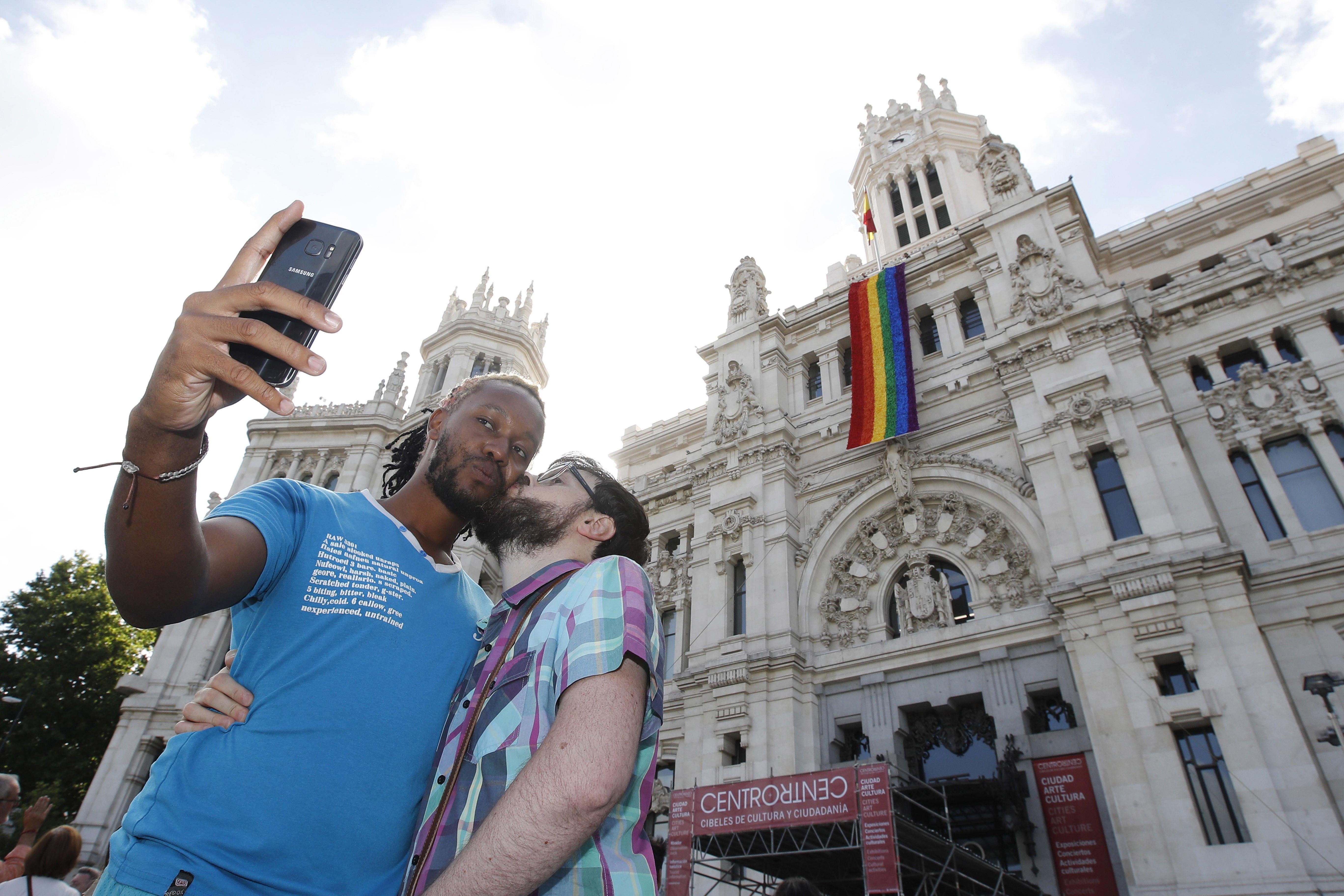 Una parella es fotografia al costat de la façana de l'Ajuntament de Madrid. /JUAN CARLOS HIDALGO