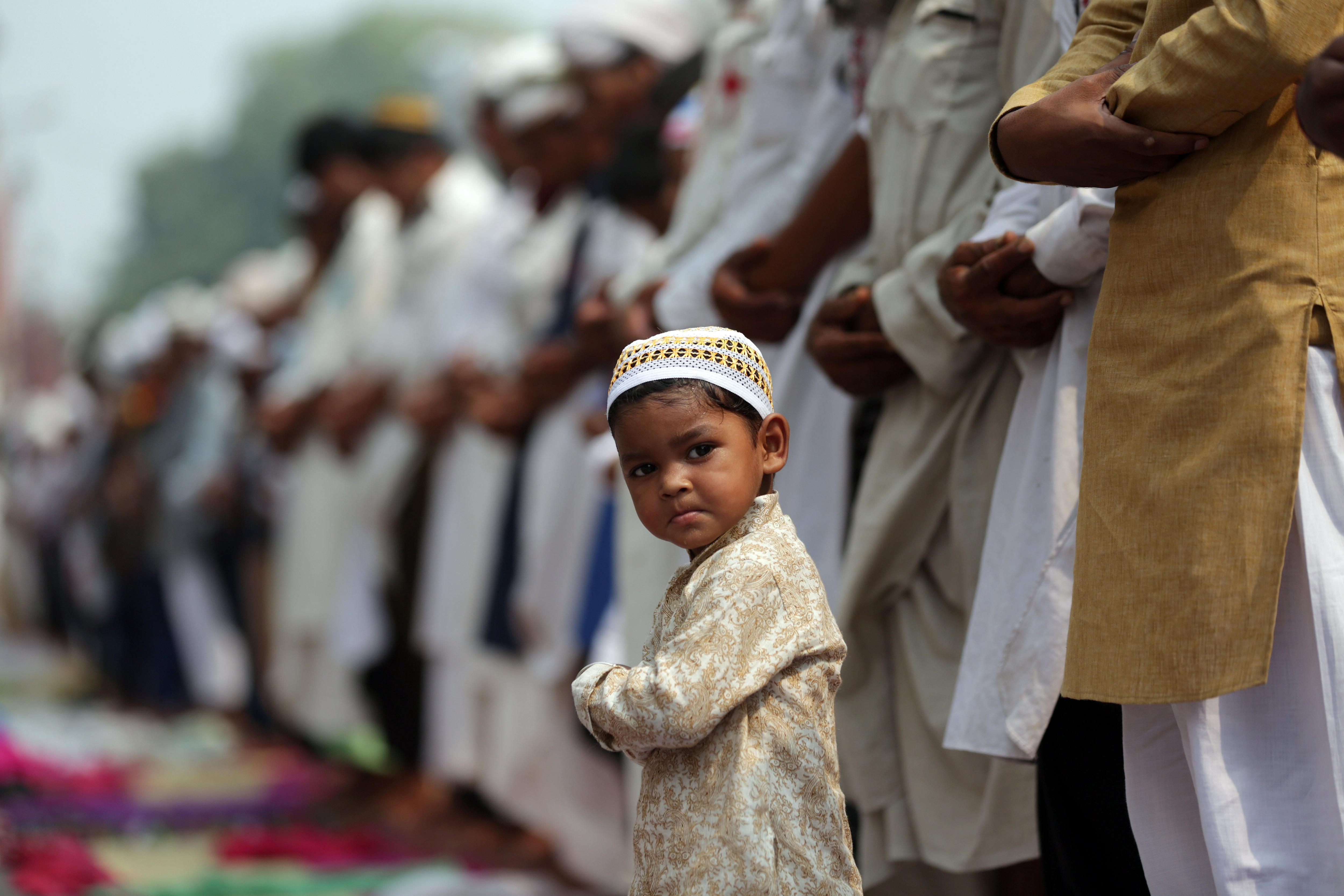 Un nin musulmà mira a càmera mentre els devots musulmans ofereixen oracions fora de la mesquita Khairudin, a Amritsar (Índia). /RAMINDER PAL SINGH