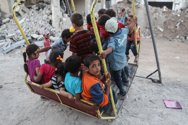 Nins immigrants juguen en un gronxador entre els enderrocs de cases destruïdes en atacs aeris a Al-Nashabiyah (Síria). /MOHAMMED BADRA