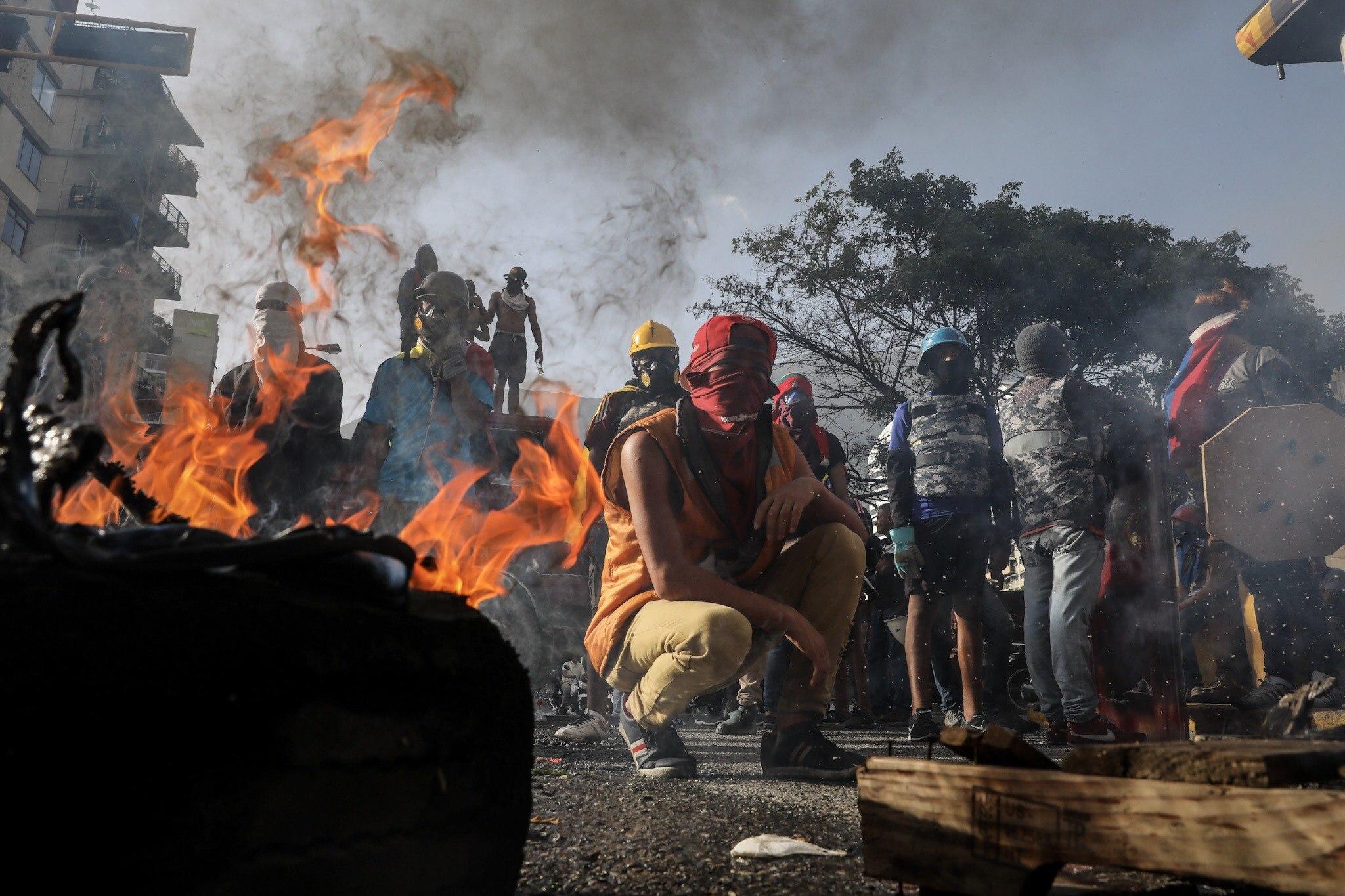 Desenes de manifestants tanquen una via amb una barricada en flames durant una protesta antigovernamental a Caracas (Veneçuela). /MIGUEL GUTIÉRREZ