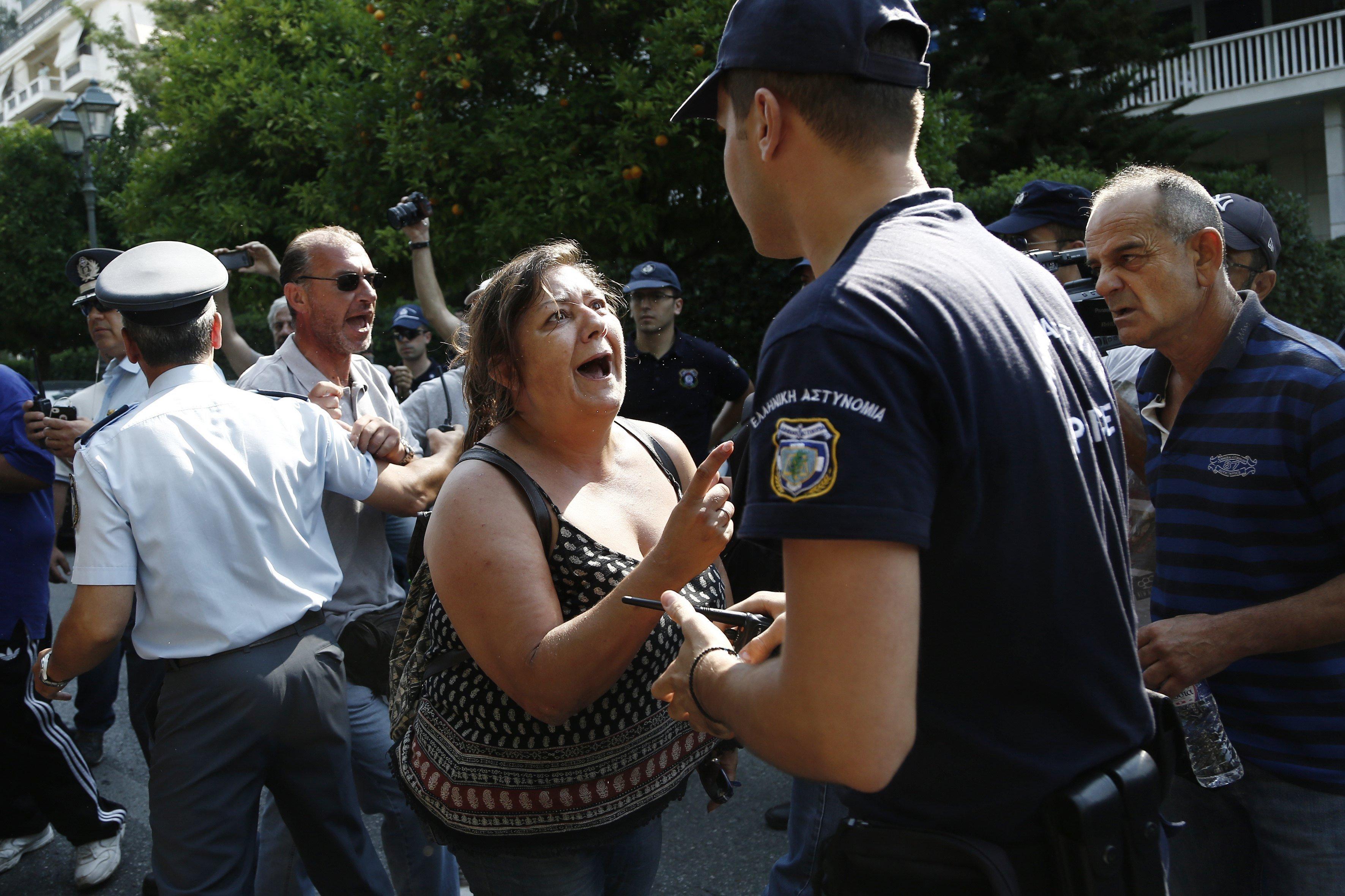 Empleats municipals s'enfronten a agents de policia mentre protesten per demanar contractes indefinits davant l'oficina del primer ministre a Atenes, Grècia. /YANNIS KOLESIDIS
