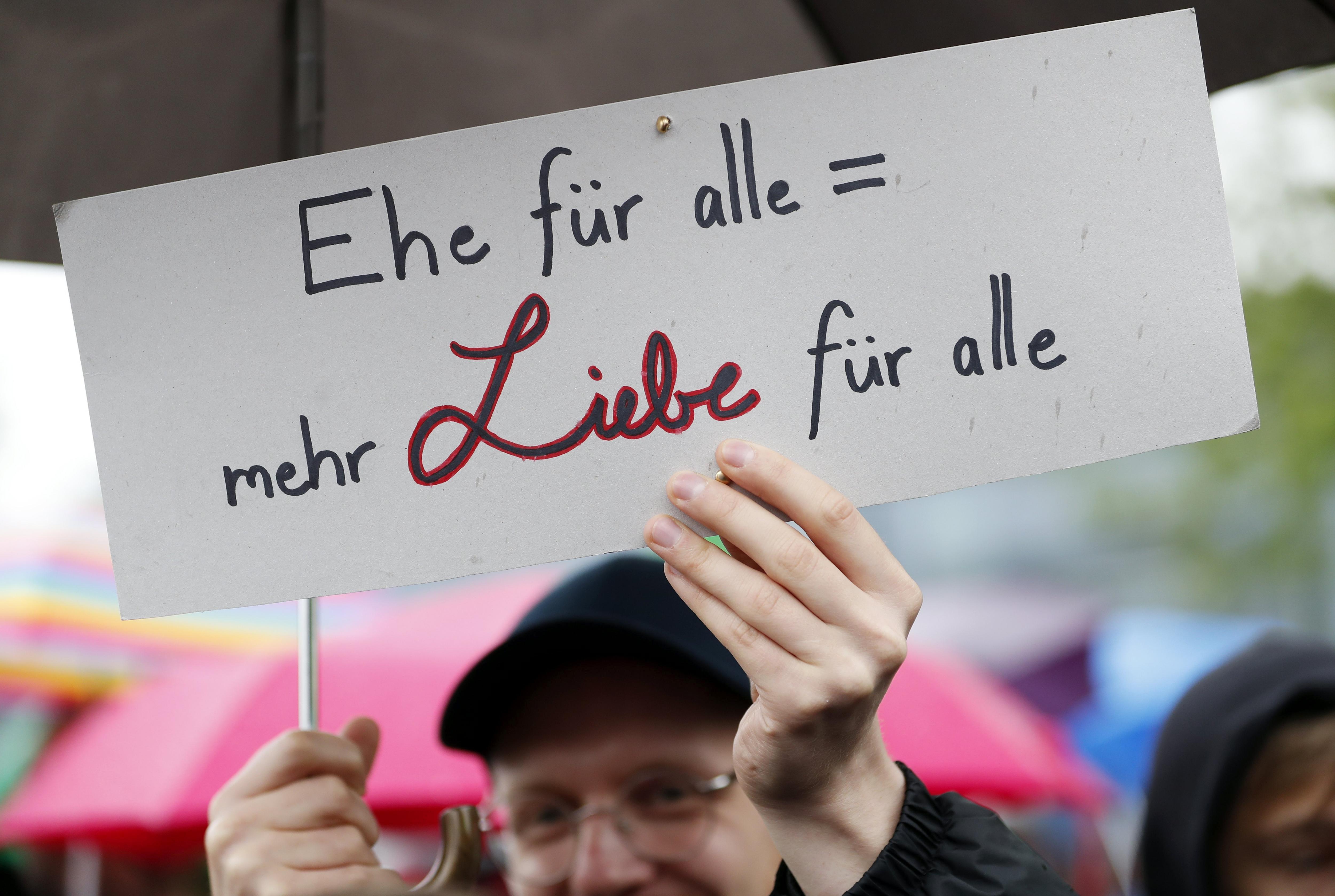 """Un home sosté una pancarta que diu """"matrimoni per a tots: més amor per tots"""" mentre diverses persones celebren l'aprovació de la legalització del matrimoni homosexual al Parlament d'Alemanya. /FELIPE TRUEBA"""