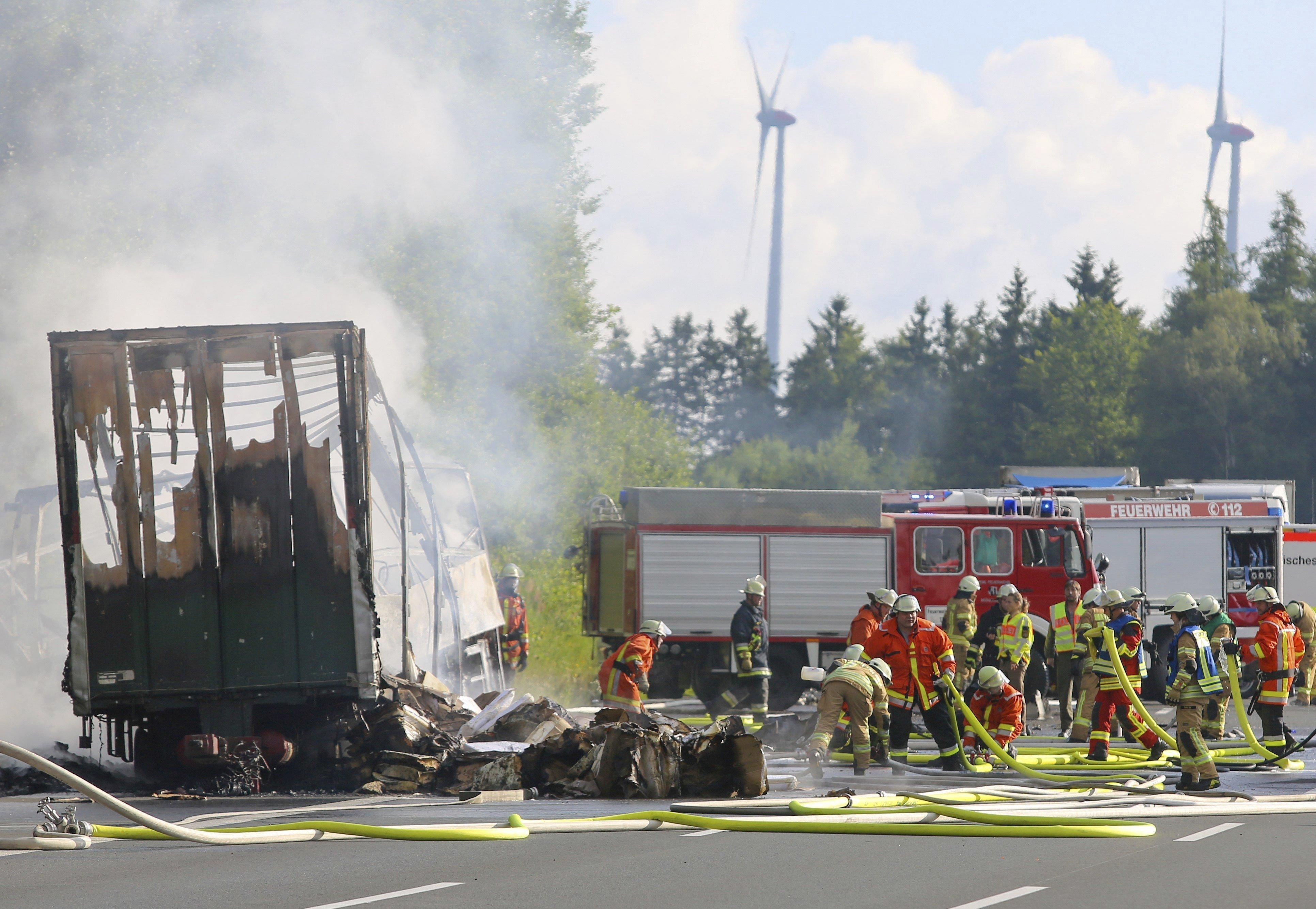 Bombers treballen al costat de les restes calcinades d'un autobús a la carretera A9 de Nuremberg, prop de Münchberg (Alemanya). STEPHAN FRICKE