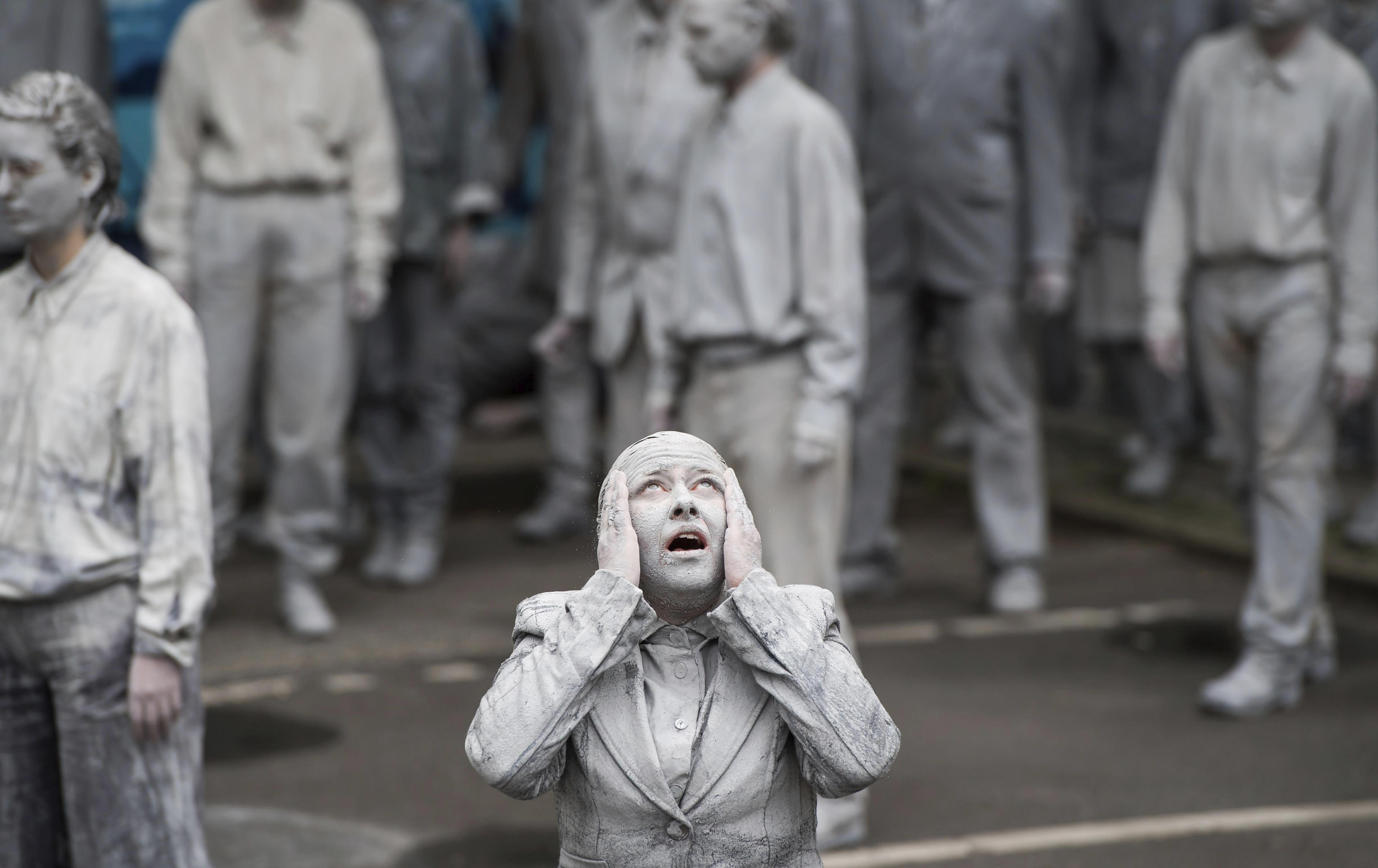 Manifestants vestits amb roba grisa i amb el pèl i la cara del mateix color participen en una protesta amb motiu del Cim de caps d'Estat i de Govern del G20 a Hamburg, Alemanya. /LUKAS BARTH-TUTTAS