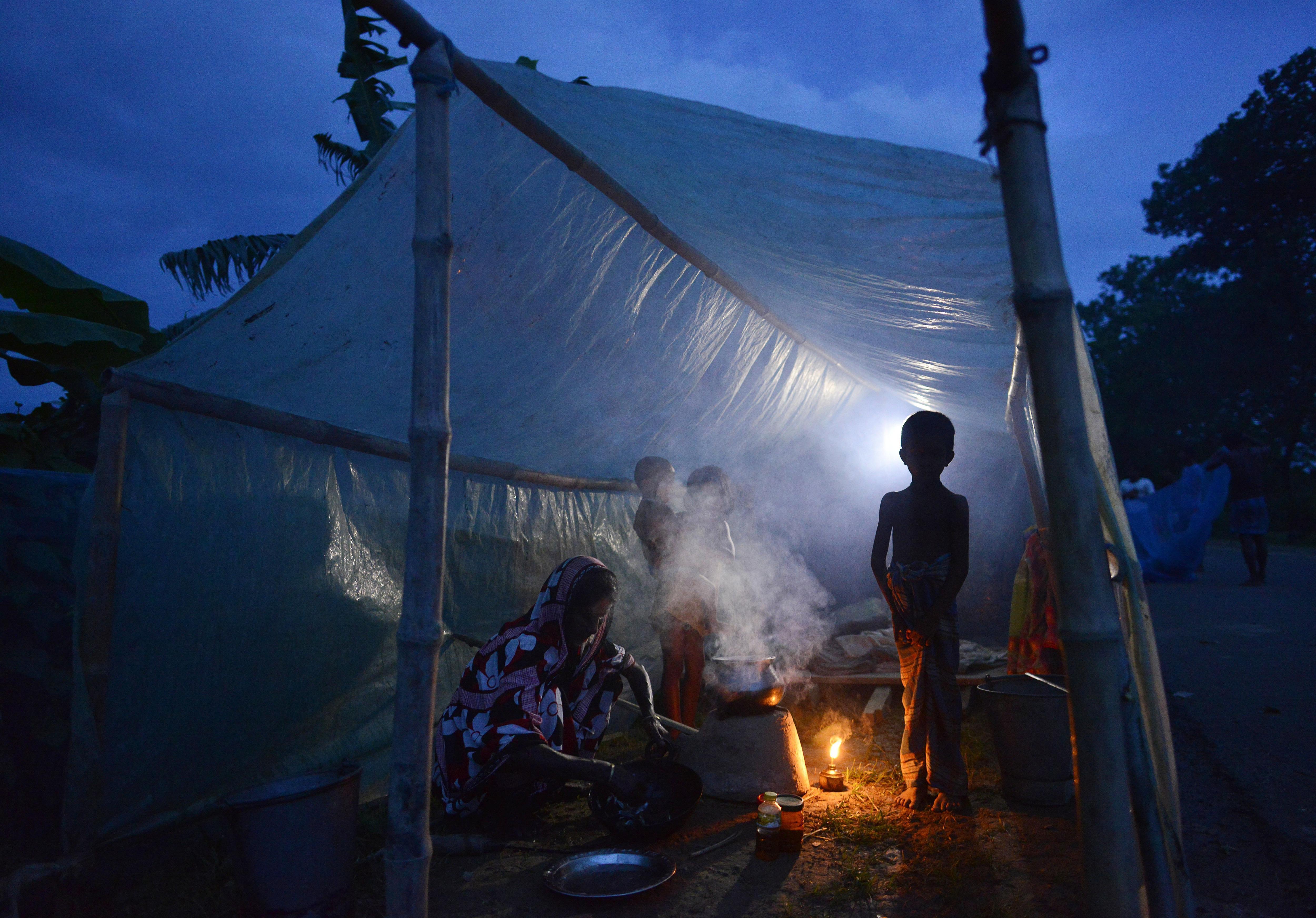 Una dona prepara el sopar en un campament improvisat després de les inundacions en el districte de Mariagaon, a l'Índia. /STR