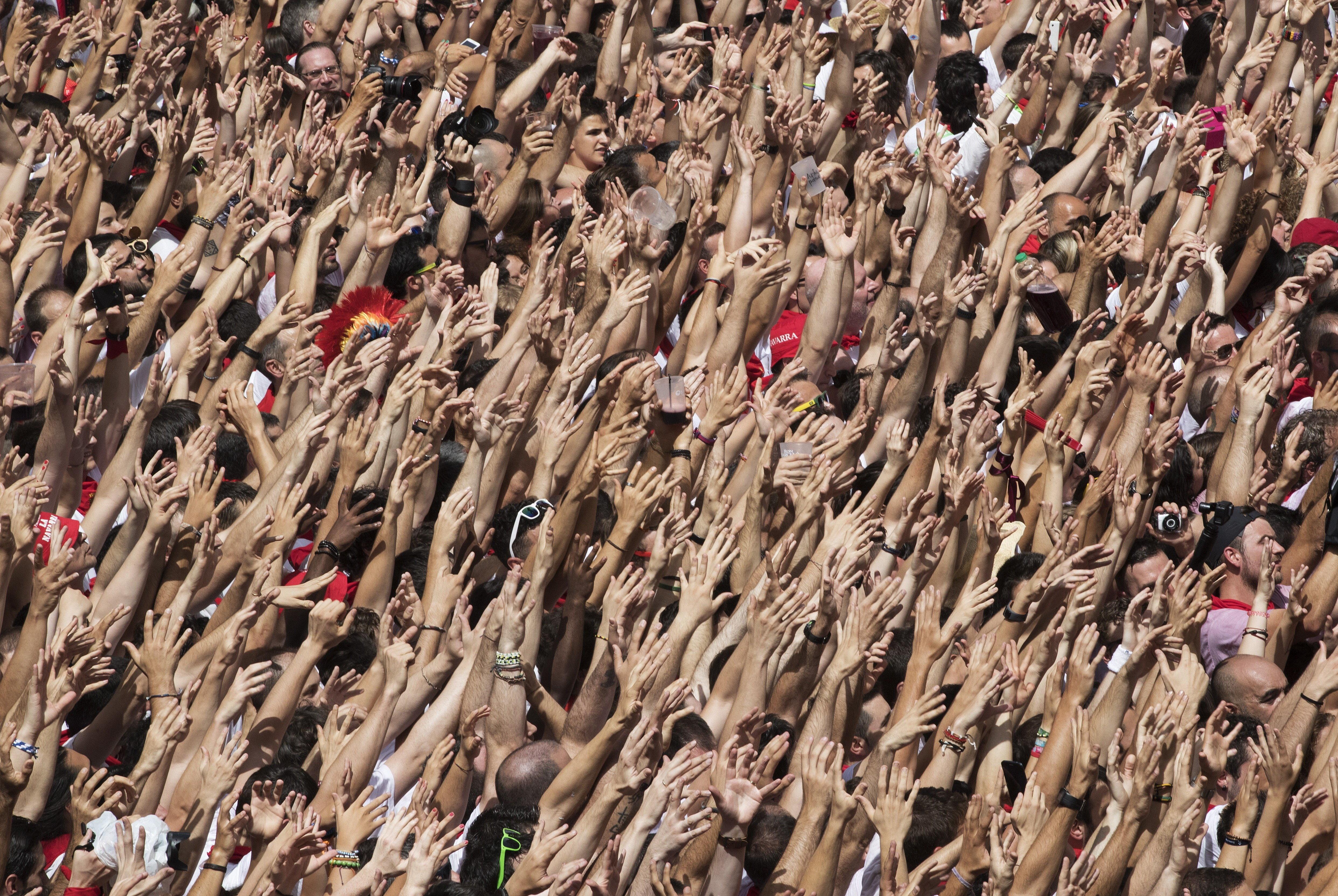Centenars de persones alcen els seus braços en sentir la música dels gaiters que surt de l'Ajuntament de Pamplona. /VILLAR LÓPEZ