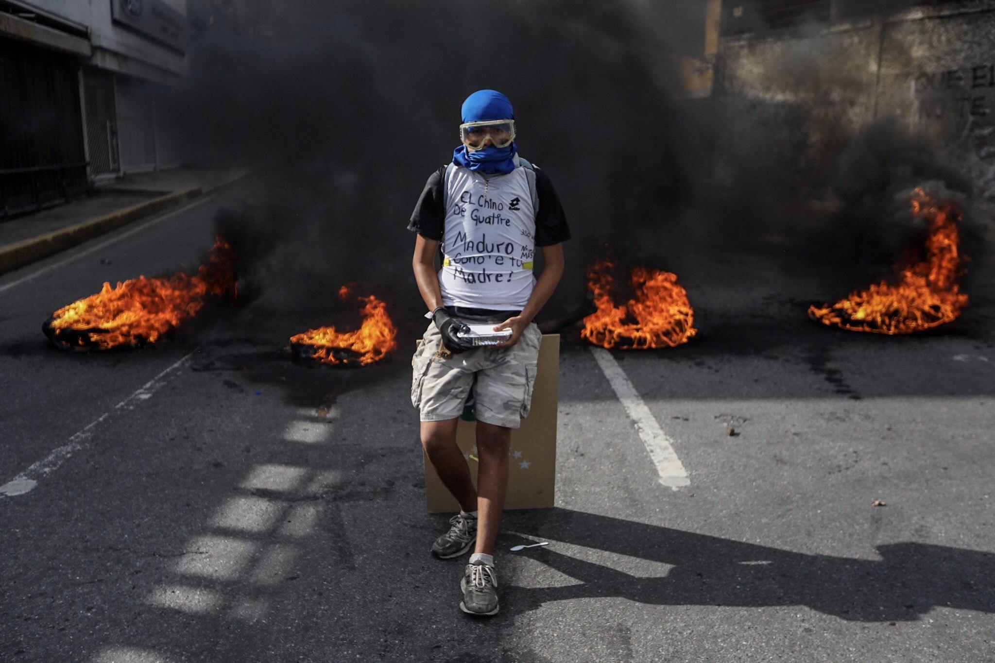 Un manifestant davant d'una barricada en flames durant una manifestació a Caracas (Veneçuela). /MIGUEL GUTIERREZ
