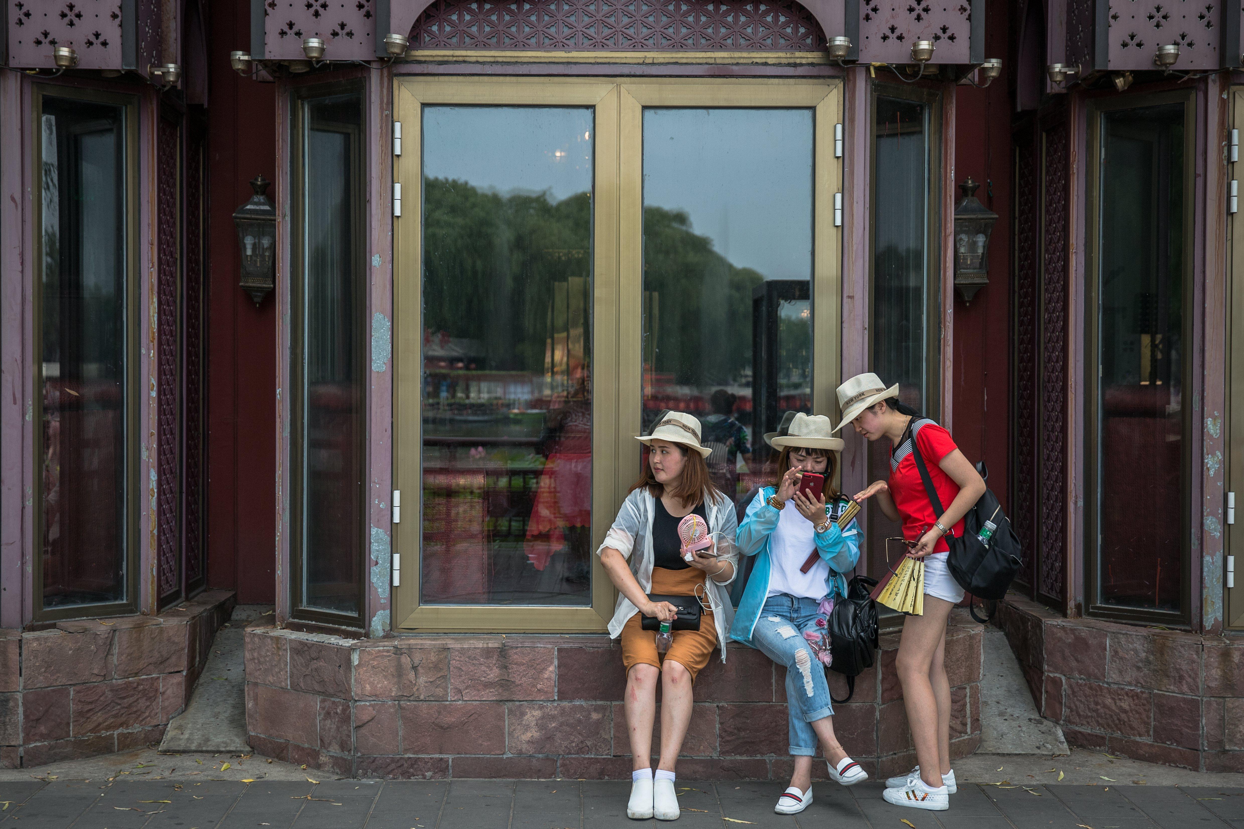 Diverses persones esperen l'autobús a Pequín (Xina) en el Dia Mundial de la Població. /ROMAN PILIPEY