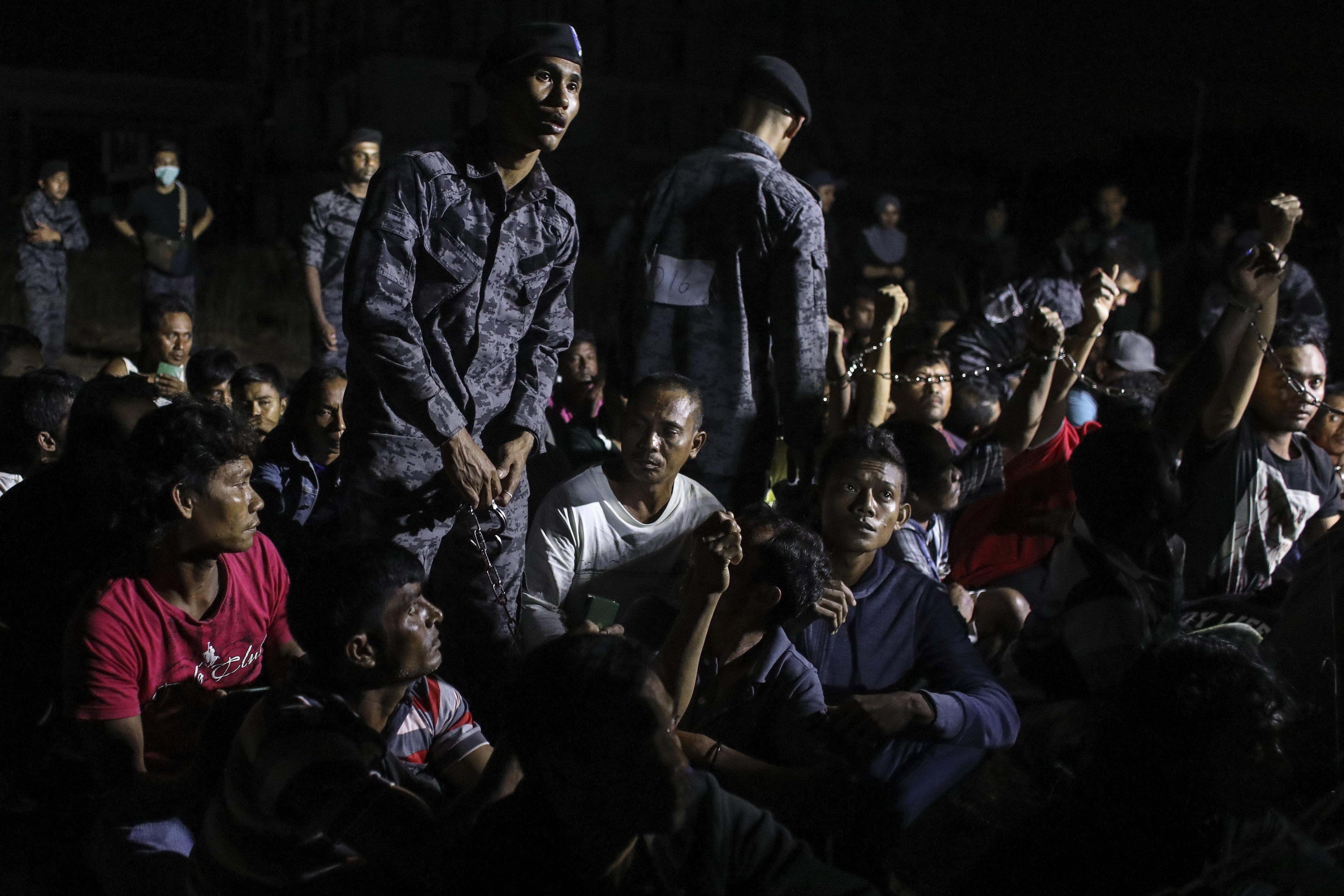 Agents d'immigració emmanillen treballadors indocumentats durant una batuda al port Dickson, Malàisia. /FAZRY ISMAIL